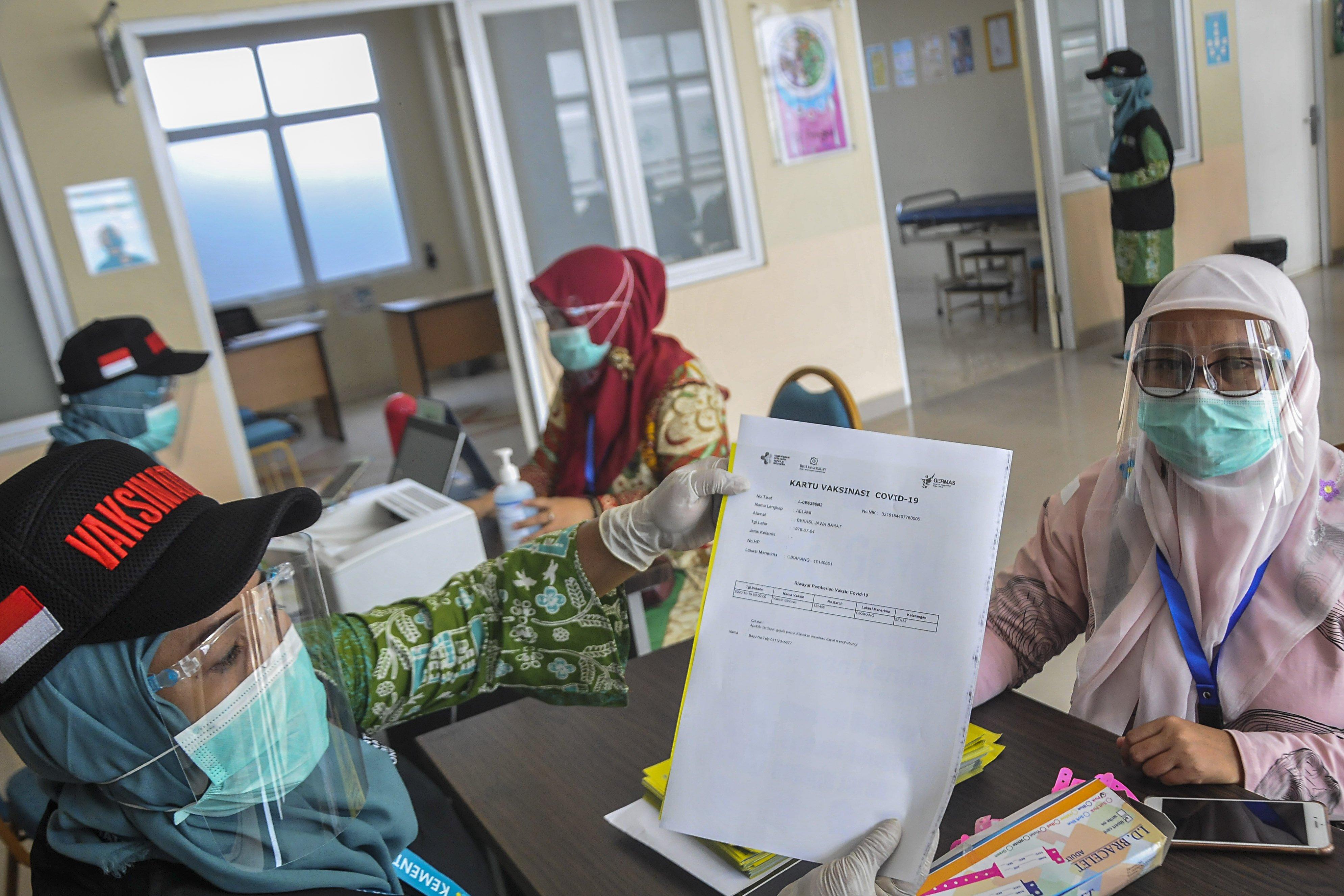 Petugas medis memberikan surat vaksinasi COVID-19 kepada warga saat simulasi di Puskesmas Cikarang, Kabupaten Bekasi, Jawa Barat, Kamis (19/11/2020). Simulasi vaksinasi COVID-19 tersebut merupakan bagian dari upaya pemerintah menyampaikan sosialisasi tentang vaksin COVID-19 yang saat ini masih dalam tahap uji klinis.