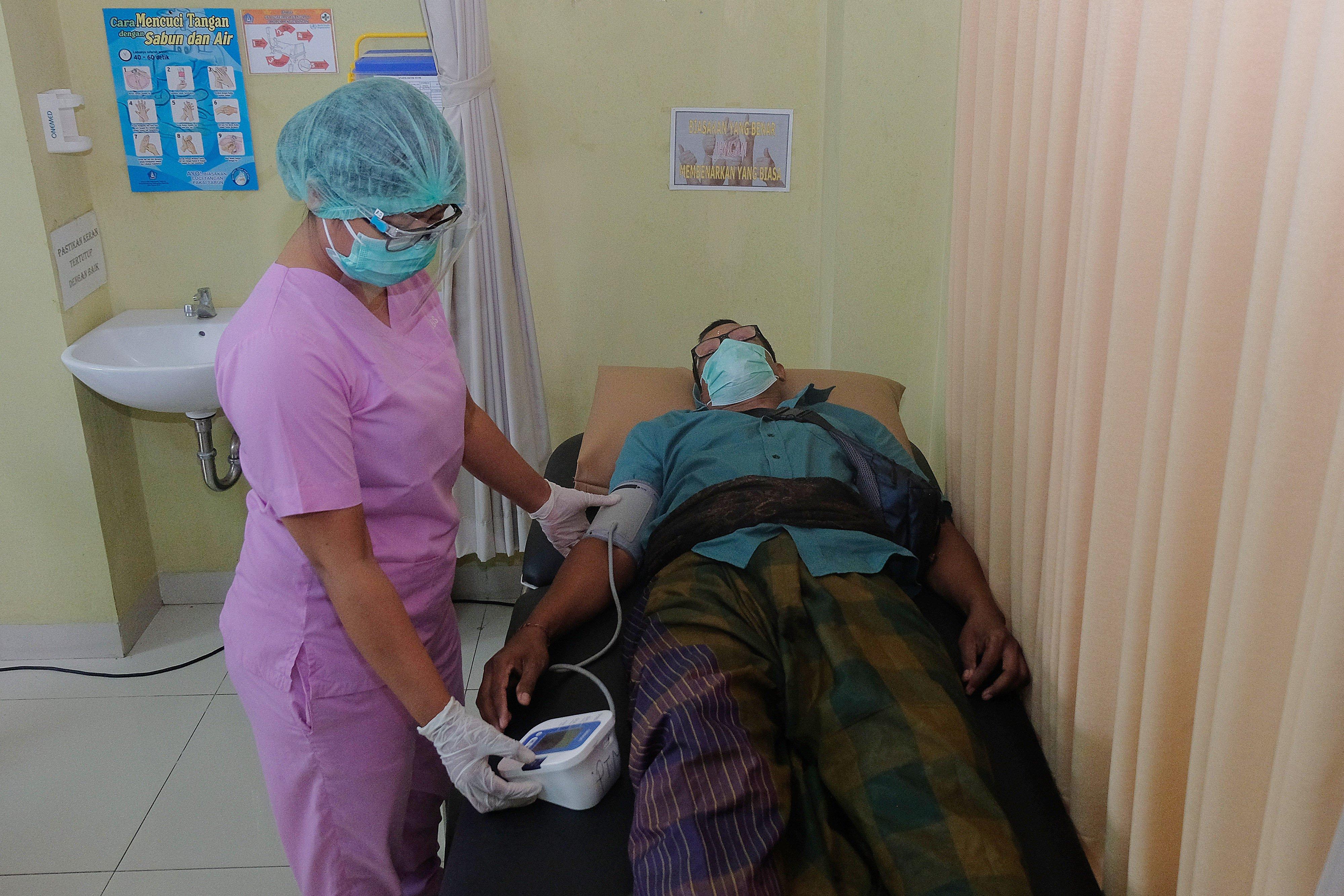 Tim medis memeriksa tensi warga dengan komorbid dalam simulasi uji coba vaksinasi COVID-19 di Puskesmas Abiansemal I, Badung, Bali, Selasa (6/10/2020). Simulasi uji coba vaksinasi COVID-19 yang diikuti puluhan warga tersebut untuk mengukur kesiapan dan kesigapan para tim medis di puskesmas itu yang rencananya dikunjungi Presiden Republik Indonesia Joko Widodo pada awal tahun depan.