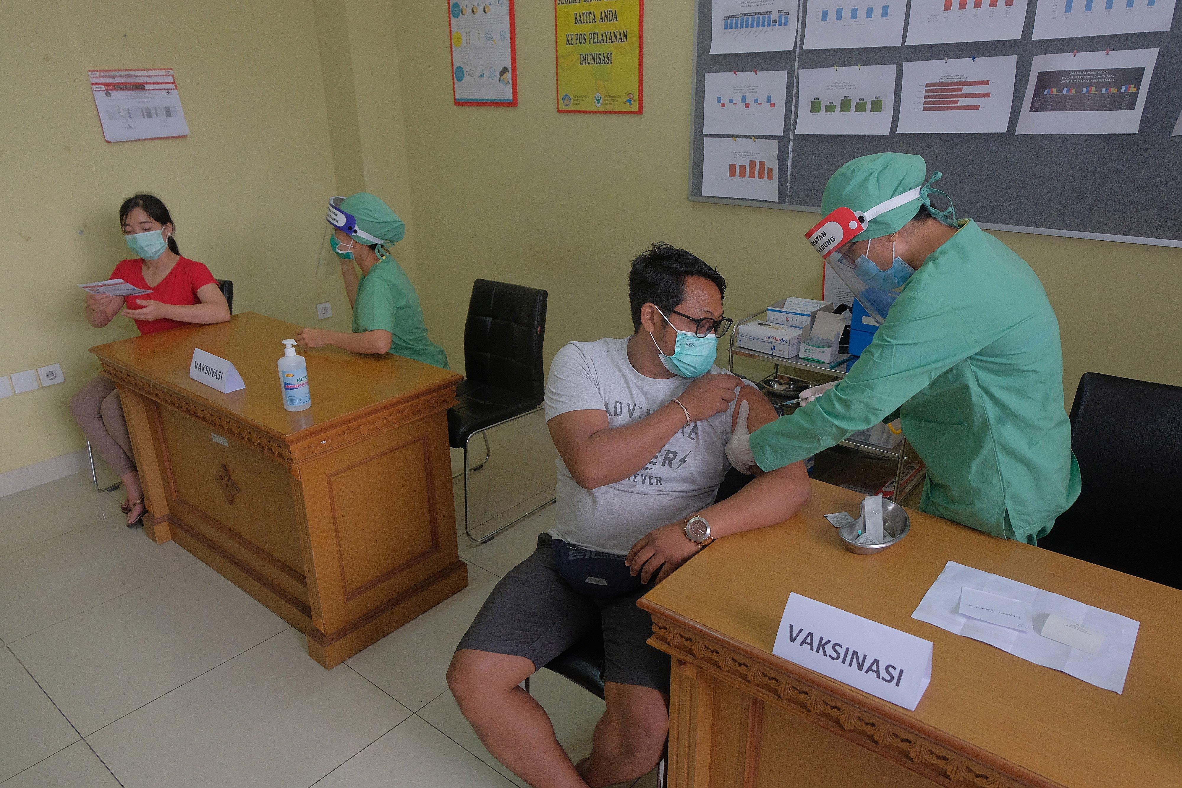 Tim medis menyuntikkan vaksin kepada sejumlah warga dalam simulasi uji coba vaksinasi COVID-19 di Puskesmas Abiansemal I, Badung, Bali, Selasa (6/10/2020). Simulasi uji coba vaksinasi COVID-19 yang diikuti puluhan warga tersebut untuk mengukur kesiapan dan kesigapan para tim medis di puskesmas itu yang rencananya dikunjungi Presiden Republik Indonesia Joko Widodo pada awal tahun depan.
