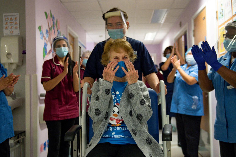 Margaret Keenan, 90, mendapat tepukan tangan dari staf saat kembali ke bangsalnya setelah menjadi orang pertama di Inggris yang menerima vaksin COVID-19 buatan Pfizer/BioNTech di Rumah Sakit Universitas, di awal program imunisasi terbesar dalam sejarah Inggris, di Coventry, Inggris, Selasa (8/12/2020). Inggris menjadi negara pertama di dunia yang memulai memvaksinasi warganya dengan vaksin buatan Pfizer/BioNTech.