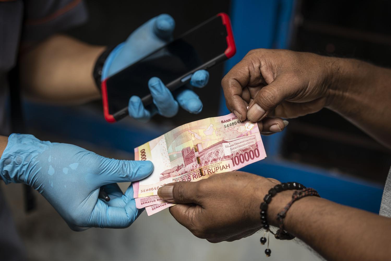 Petugas PT Pos Indonesia menyalurkan Bantuan Sosial Tunai (BST) kepada warga RW 05 di kawasan Kelurahan Kenari, Senen, Jakarta, Rabu (6/1/2021). Pemerintah mulai menyalurkan Bantuan Sosial Tunai (BST) tahun 2021 untuk empat bulan kedepan senilai Rp300 ribu per Keluarga Penerima Manfaat (KPM) yang diberikan secara langsung kepada warga melalui petugas PT Pos Indonesia dan bank-bank milik negara.