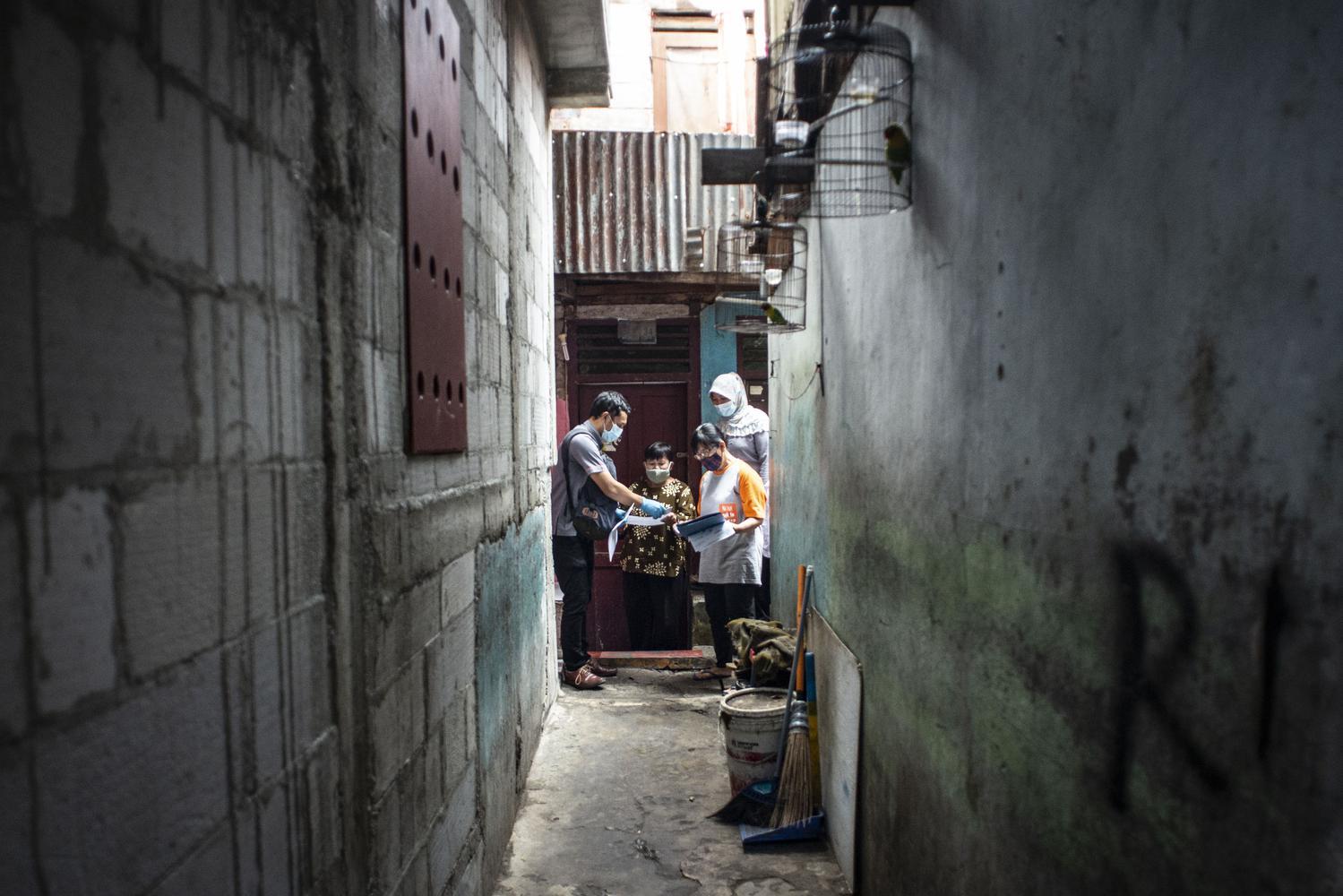 Petugas PT Pos Indonesia (kiri) menyalurkan Bantuan Sosial Tunai (BST) kepada warga RW 05 di Senen, Jakarta, Rabu (6/1/2021). Pemerintah mulai menyalurkan Bantuan Sosial Tunai (BST) tahun 2021 untuk empat bulan kedepan senilai Rp300 ribu per Keluarga Penerima Manfaat (KPM) yang diberikan secara langsung kepada warga melalui petugas PT Pos Indonesia dan bank-bank milik negara.