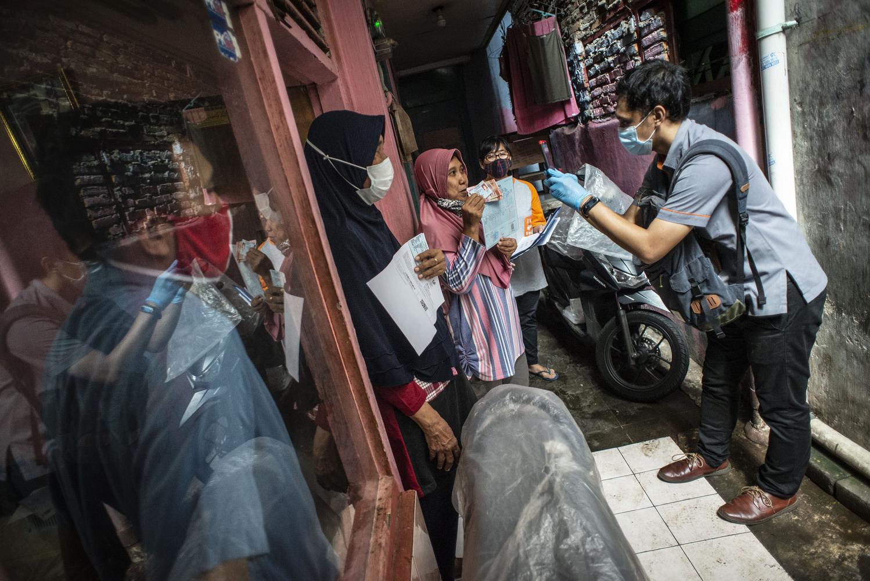 Petugas PT Pos Indonesia (kanan) memotret wajah warga RW 05 yang telah menerima Bantuan Sosial Tunai (BST) di Senen, Jakarta, Rabu (6/1/2021). Pemerintah mulai menyalurkan Bantuan Sosial Tunai (BST) tahun 2021 untuk empat bulan kedepan senilai Rp300 ribu per Keluarga Penerima Manfaat (KPM) yang diberikan secara langsung kepada warga melalui petugas PT Pos Indonesia dan bank-bank milik negara.