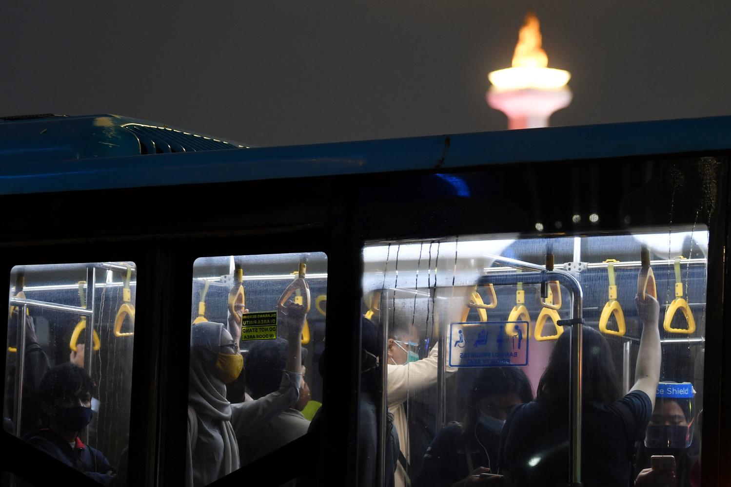 Penumpang menaiki Bus Transjakarta saat melintasi kawasan Pantung Arjuna Wiwaha, Jakarta, Rabu (6/1/2021). Pemerintah melakukan pengetatan pembatasan pergerakan di Jawa dan Bali pada 11-25 Januari 2021 untuk menekan penyebaran COVID-19, diantaranya dengan melakukan pembatasan kapasitas dan operasional transportasi umum.
