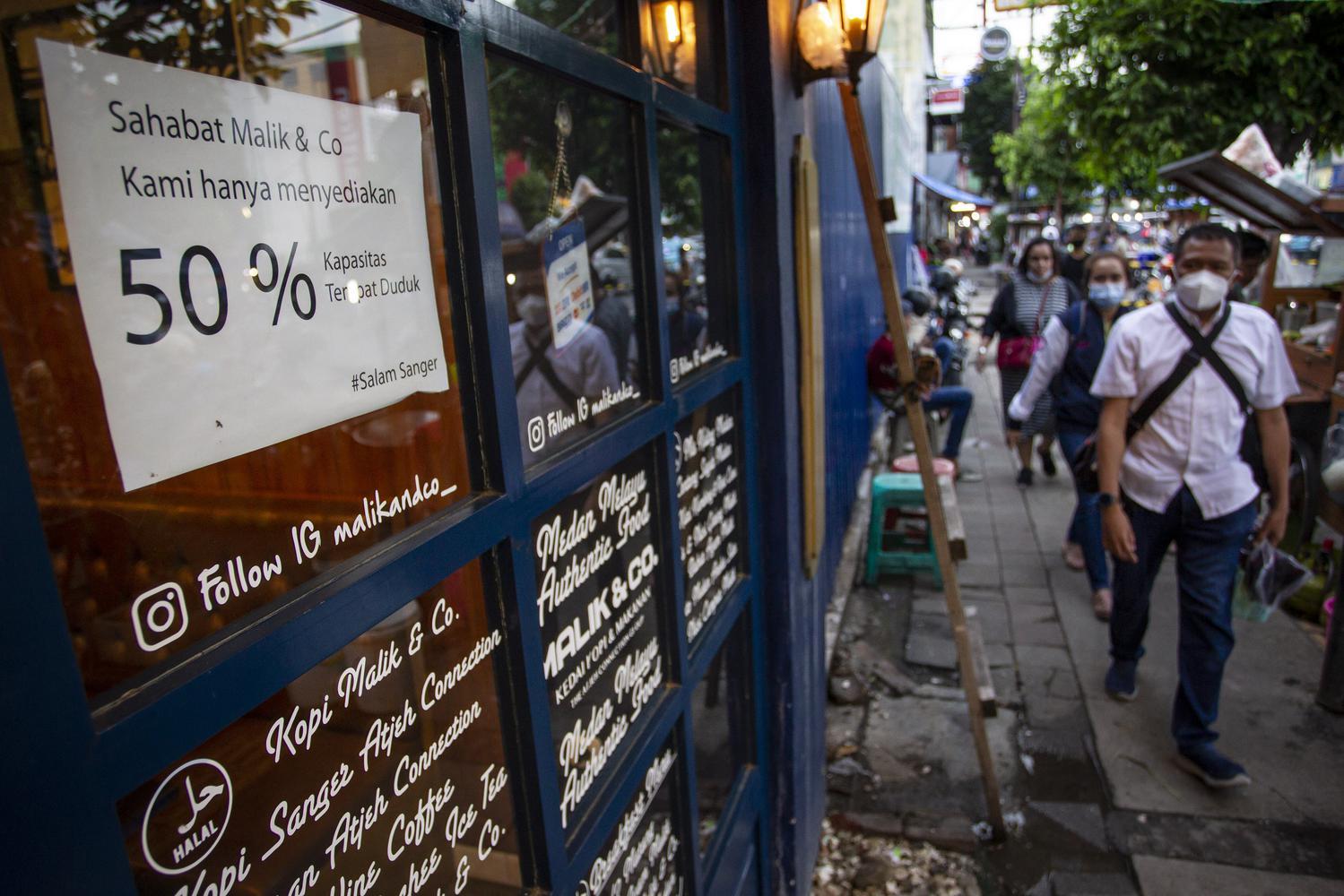 Warga berjalan di depan salah satu restoran di kawasan Sabang, Jakarta, Jumat (8/1/2021). Pemerintah menetapkan kebijakan Pemberlakuan Pembatasan Kegiatan Masyarakat (PPKM) di wilayah Jawa-Bali pada 11-25 Januari mendatang guna menekan angka penularan COVID-19 yang salah satunya membatasi kegiatan di restoran untuk makan atau minum di tempat hanya diperbolehkan sebanyak 25 persen dari kapasitas.