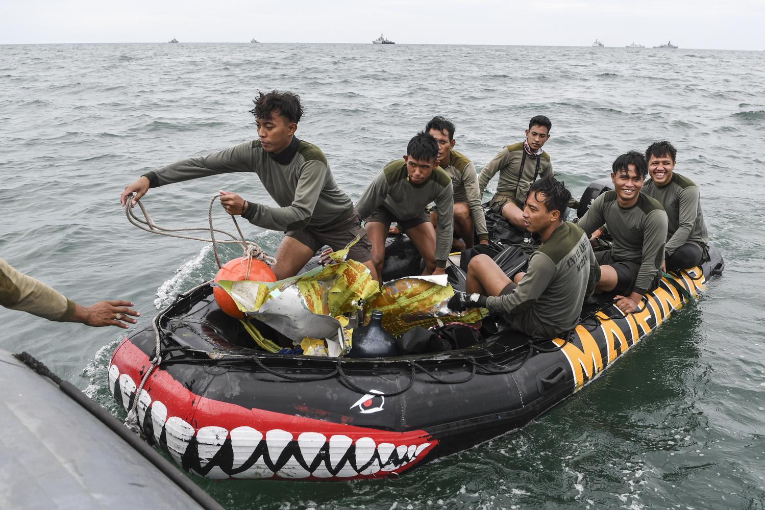 Sejumlah prajurit Batalyon Intai Amfibi 1 Korps Marinir (Yontaifib) TNI AL mengangkut serpihan dari pesawat Sriwijaya Air SJ 182 yang hilang kontak saat melakukan pencarian di perairan Kepulauan Seribu, Jakarta, Minggu (10/1/2021). Pesawat Sriwijaya Air SJ 182 yang hilang kontak pada Sabtu (9/1) sekitar pukul 14.40 WIB di ketinggian 10 ribu kaki tersebut membawa enam awak dan 56 penumpang.
