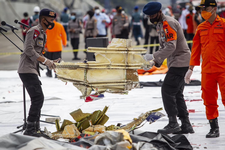 Polisi membawa bagian pesawat Sriwijaya Air SJ182 rute Jakarta - Pontianak yang jatuh di perairan Pulau Seribu di Dermaga JICT, Tanjung Priok, Jakarta Utara, Minggu (10/1/2021). Temuan bagian pesawat selanjutnya akan diperiksa oleh Komite Nasional Keselamatan Transportasi (KNKT) sedangkan potongan tubuh korban diserahkan kepada DVI Polri untuk identifikasi lebih lanjut.