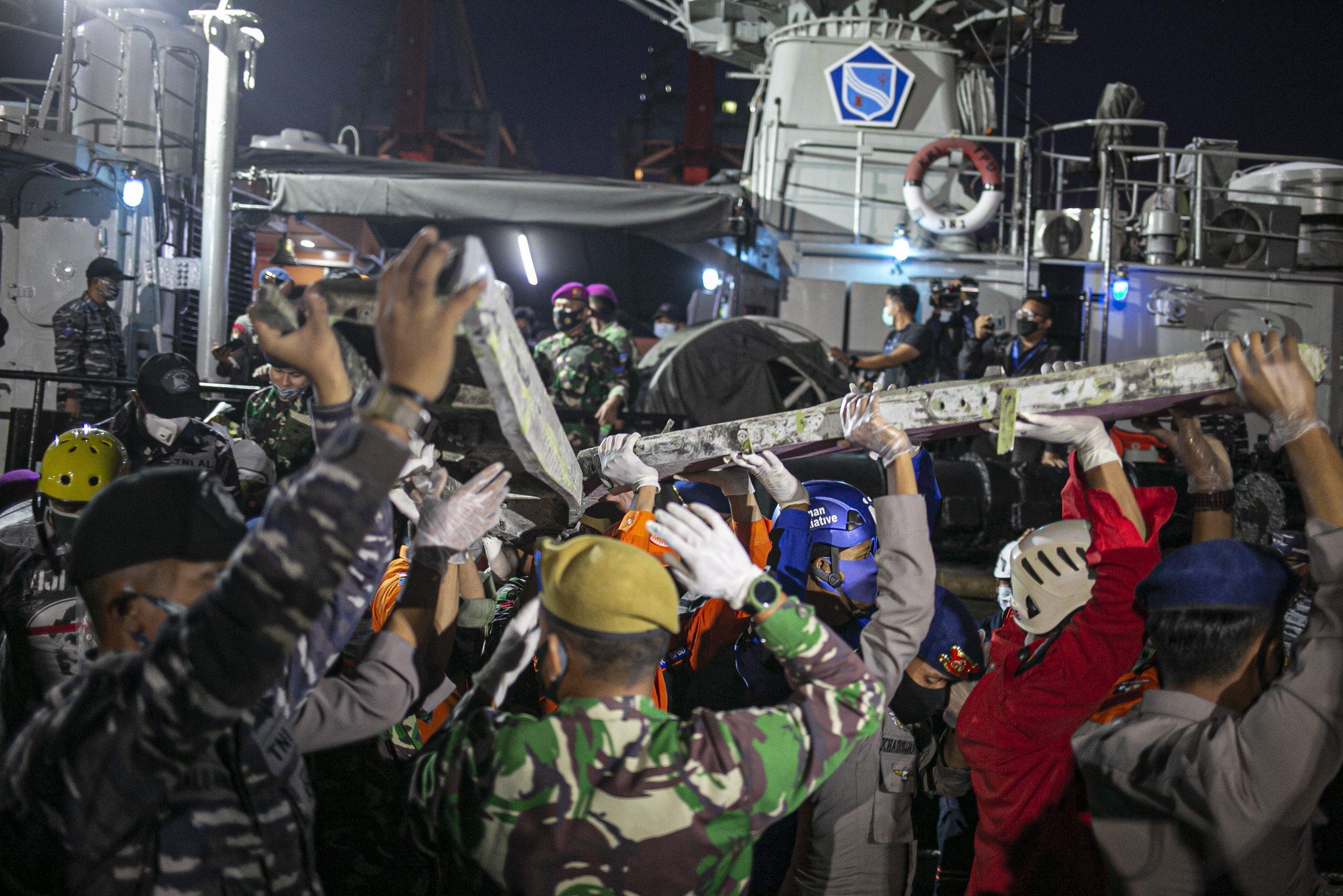 Petugas membawa bagian pesawat Sriwijaya Air SJ182 rute Jakarta - Pontianak yang jatuh di perairan Pulau Seribu di Dermaga JICT, Tanjung Priok, Jakarta Utara, Minggu (10/1/2021). Temuan bagian pesawat selanjutnya akan diperiksa oleh Komite Nasional Keselamatan Transportasi (KNKT) sedangkan potongan tubuh korban diserahkan kepada DVI Polri untuk identifikasi lebih lanjut.