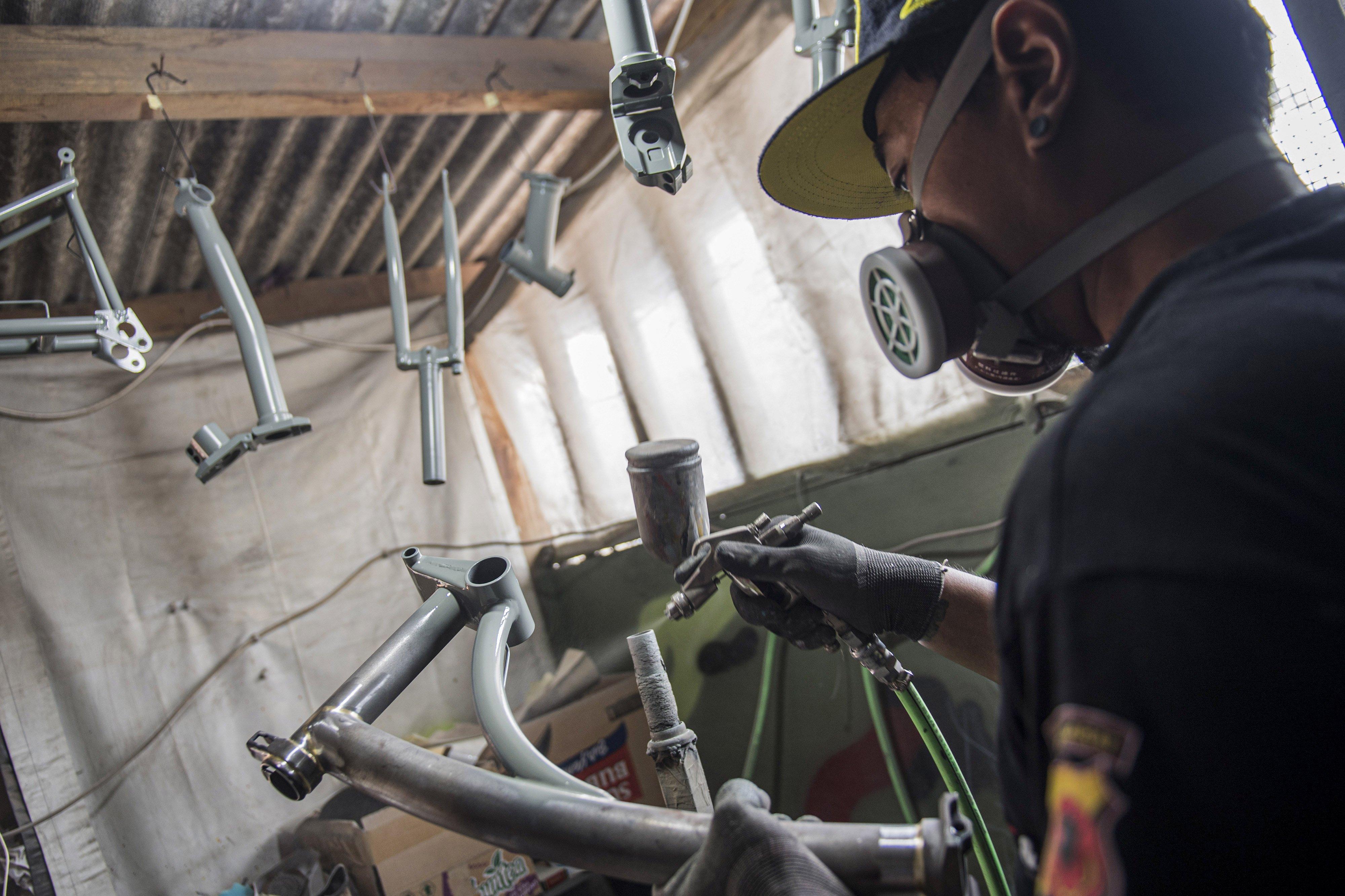 Pekerja mengecat rangka (main frame) sepeda lipat Kreuz di Bandung, Jawa Barat, Senin (23/11/2020).