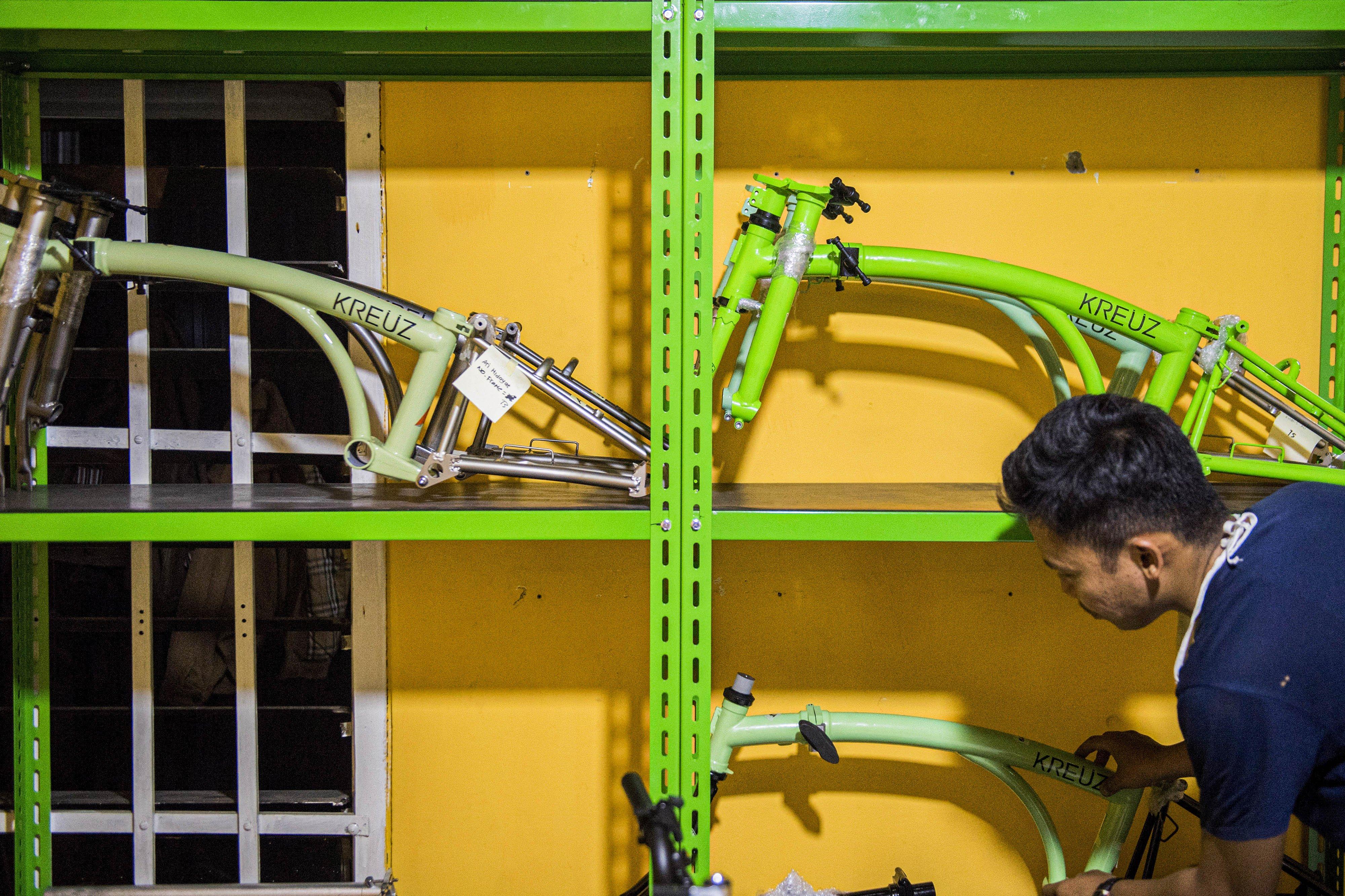Pekerja menata rangka (main frame) sepeda lipat Kreuz seusai pengecatan di Bandung, Jawa Barat, Jumat (20/11/2020).