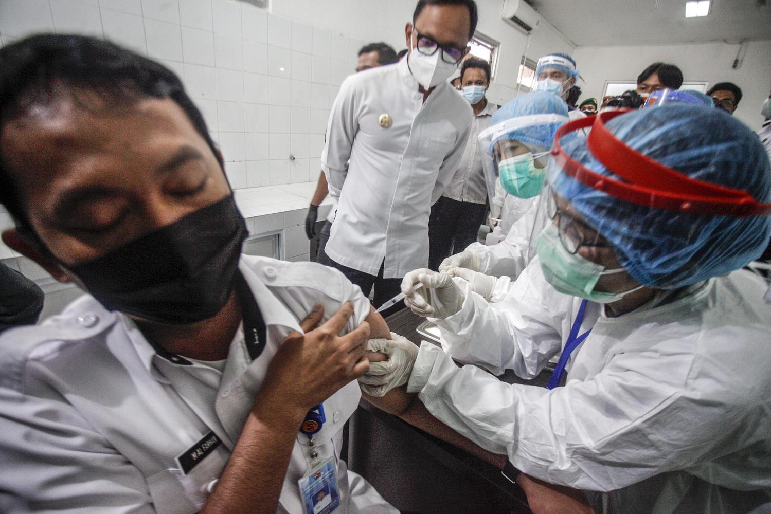 Petugas medis menyuntikan vaksin COVID-19 ke seorang tenaga kesehatan disaksikan Wali Kota Bogor Bima Arya (tengah) di RSUD Kota Bogor, Bogor, Jawa Barat, Kamis (14/1/2021). Sebanyak 1,2 juta tenaga kesehatan yang selama ini menjadi garda terdepan dalam penanganan pandemi COVID-19 di Indonesia, menjalani vaksinasi Covid-19 tahap pertama yang dimulai Rabu (13/1).