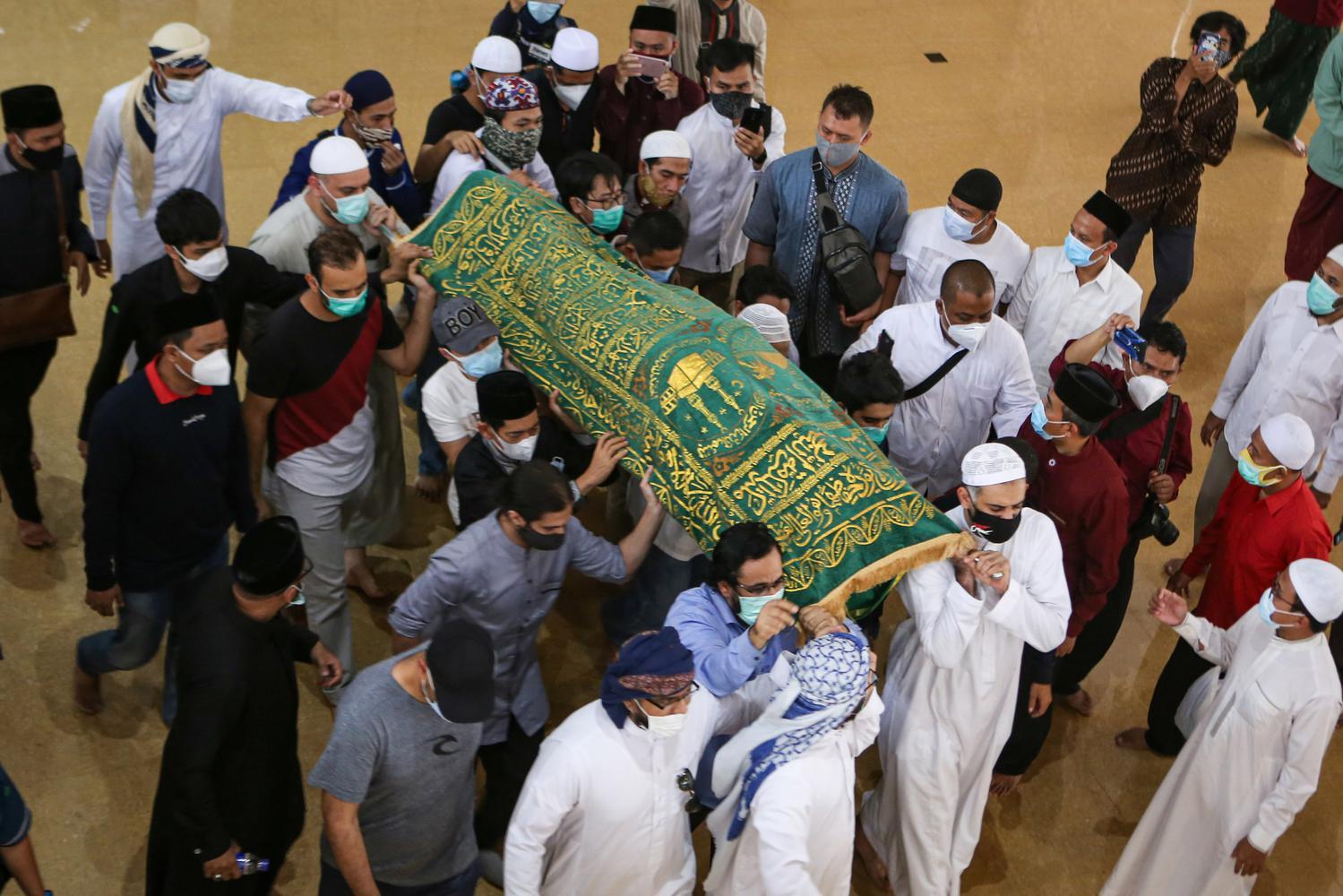 Sejumlah keluarga dan kerabat mengusung jenazah Syekh Ali Jaber menuju tempat pemakaman usai disalatkan di Pesantren Daarul Quran, Cipondoh, Kota Tangerang, Banten, Kamis (14/1/2021). Syekh Ali Jeber meninggal dunia di usia 44 tahun akibat sakit.