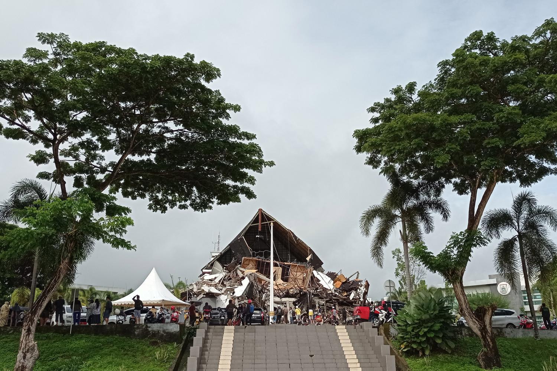 Warga mengamati Gedung Kantor Gubernur Sulawesi Barat yang rusak akibat gempa bumi, di Mamuju, Sulawesi Barat, Jumat (15/1/2021). Petugas BPBD SUlawesi Barat masih mendata jumlah kerusakan dan korban akibat gempa bumi berkekuatan magnitudo 6,2 tersebut.