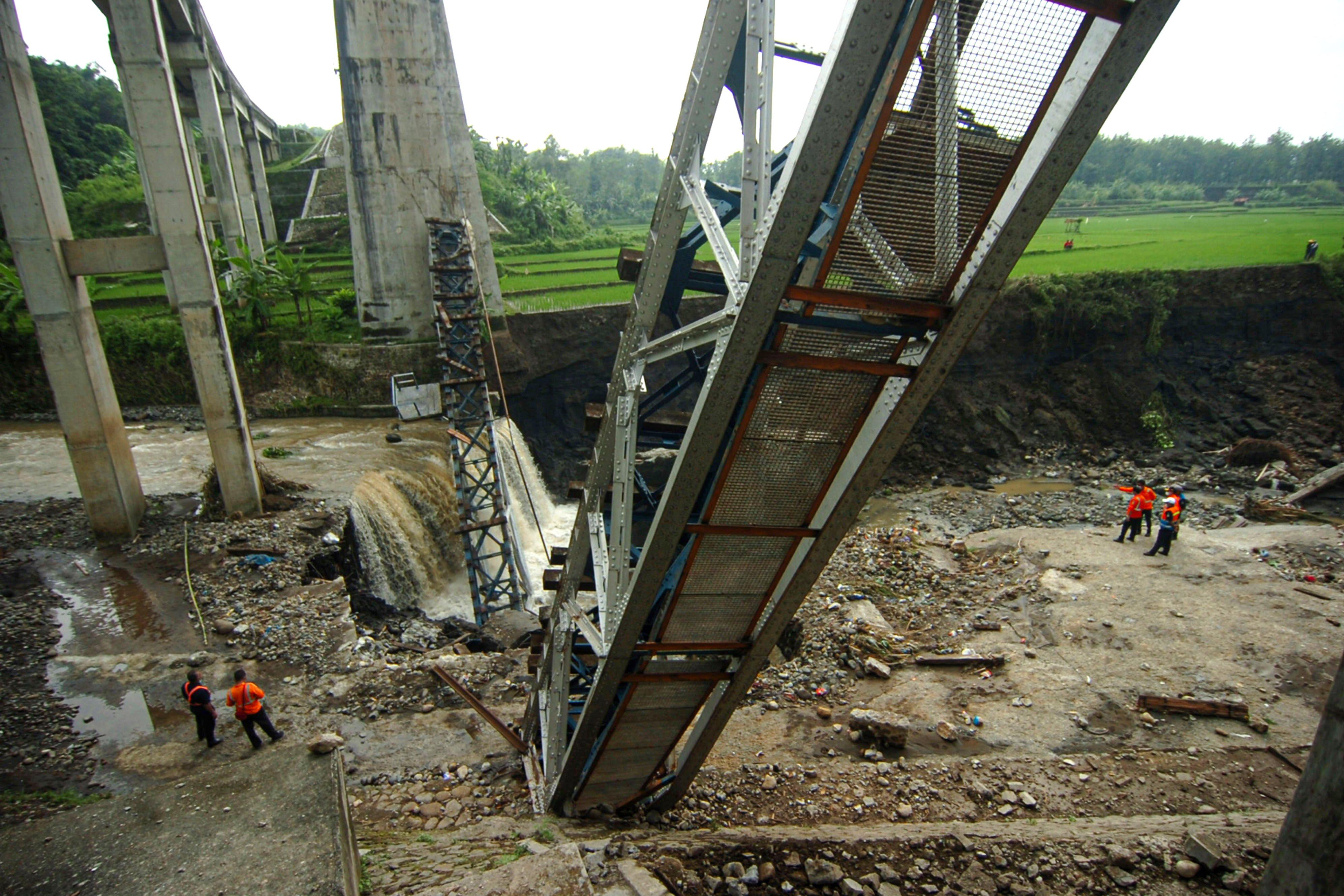 Petugas PT KAI memeriksa jembatan rel Kereta Api (KA) yang ambruk di Dukuh Timbang, Desa Tonjong, Brebes, Jawa Tengah, Selasa (12/1/2021). Jembatan sepanjang 50 meter dengan tinggi 22 meter yang menghubungkan Jakarta-Yogyakarta-Surabaya via jalur Selatan tersebut ambruk akibat diterjang banjir Sungai Glagah.