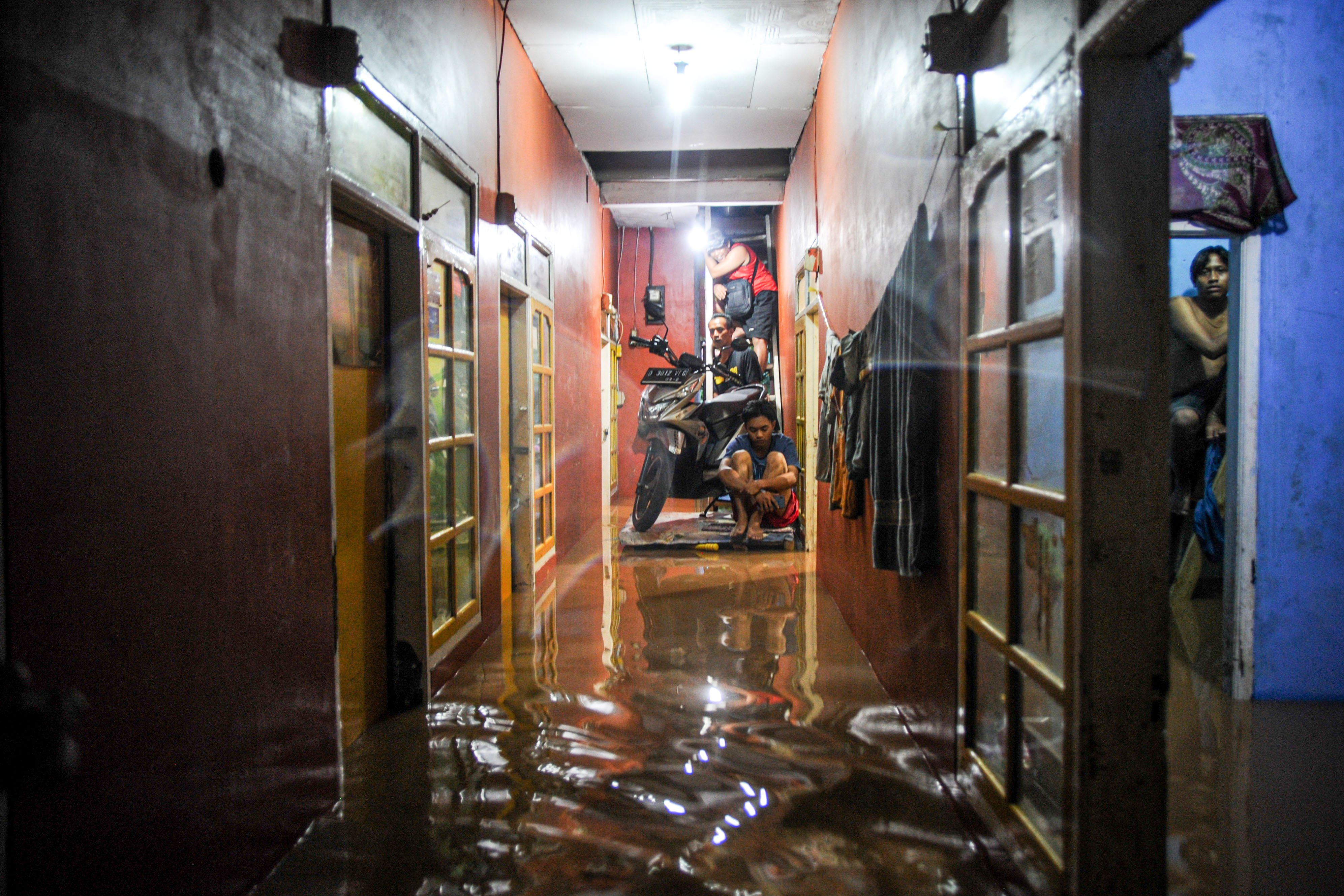 Aktivitas warga saat rumahnya terendam banjir di Dangdeur, Rancaekek, Kabupaten Bandung, Jawa Barat, Sabtu (9/1/2021). Genangan air setinggi 60 hingga 150 sentimeter membanjiri puluhan permukiman warga di Rancaekek akibat hujan lebat yang mengguyur Bandung Raya pada Sabtu (9/1) siang hingga sore hari.