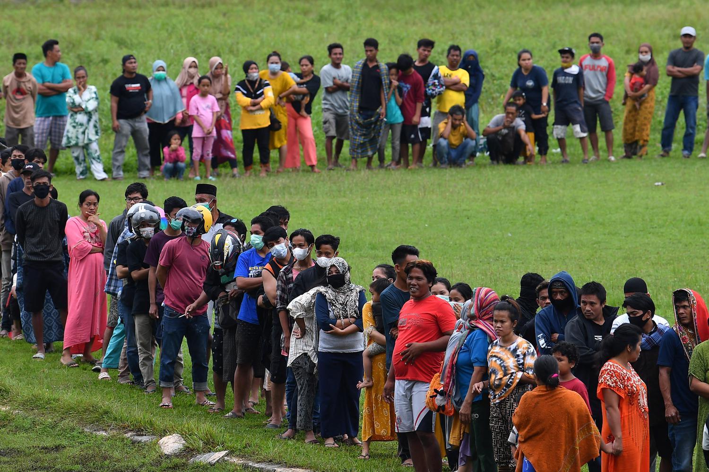 Pengungsi korban gempa antre untuk mendapatkan bantuan logistik dari TNI AD di Stadion Manakarra, Mamuju, Sulawesi Barat, Minggu (17/1/2021). Berdasarkan data BNPB per 17 Januari pukul 14.00 WIB, jumlah korban meninggal dunia akibat gempa bumi magnitudo 6,2 di Sulawesi Barat telah mencapai 73 orang.