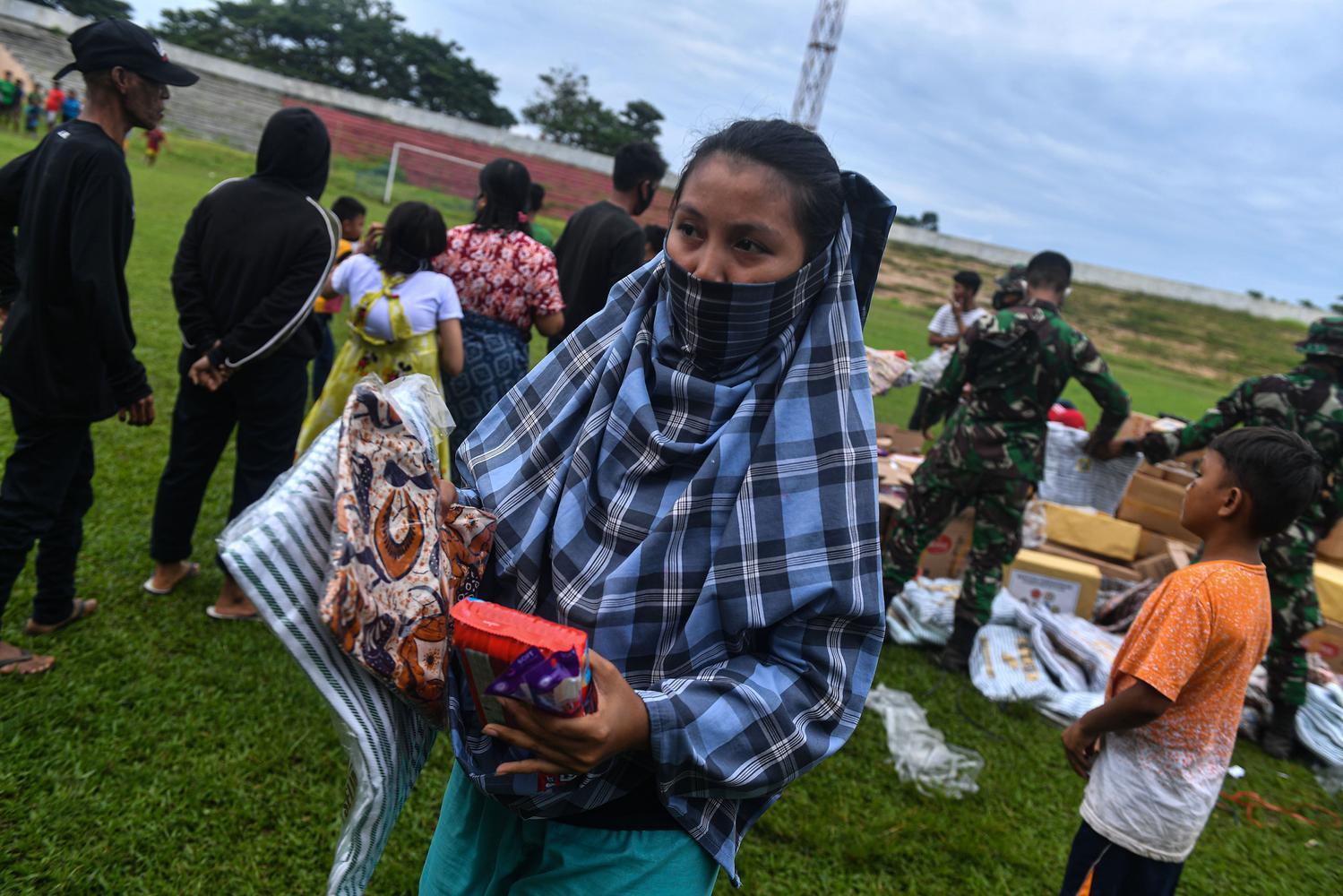 Pengungsi korban gempa membawa bantuan logistik dari TNI AD di Stadion Manakarra, Mamuju, Sulawesi Barat, Minggu (17/1/2021). Berdasarkan data BNPB per 17 Januari pukul 14.00 WIB, jumlah korban meninggal dunia akibat gempa bumi magnitudo 6,2 di Sulawesi Barat telah mencapai 73 orang.