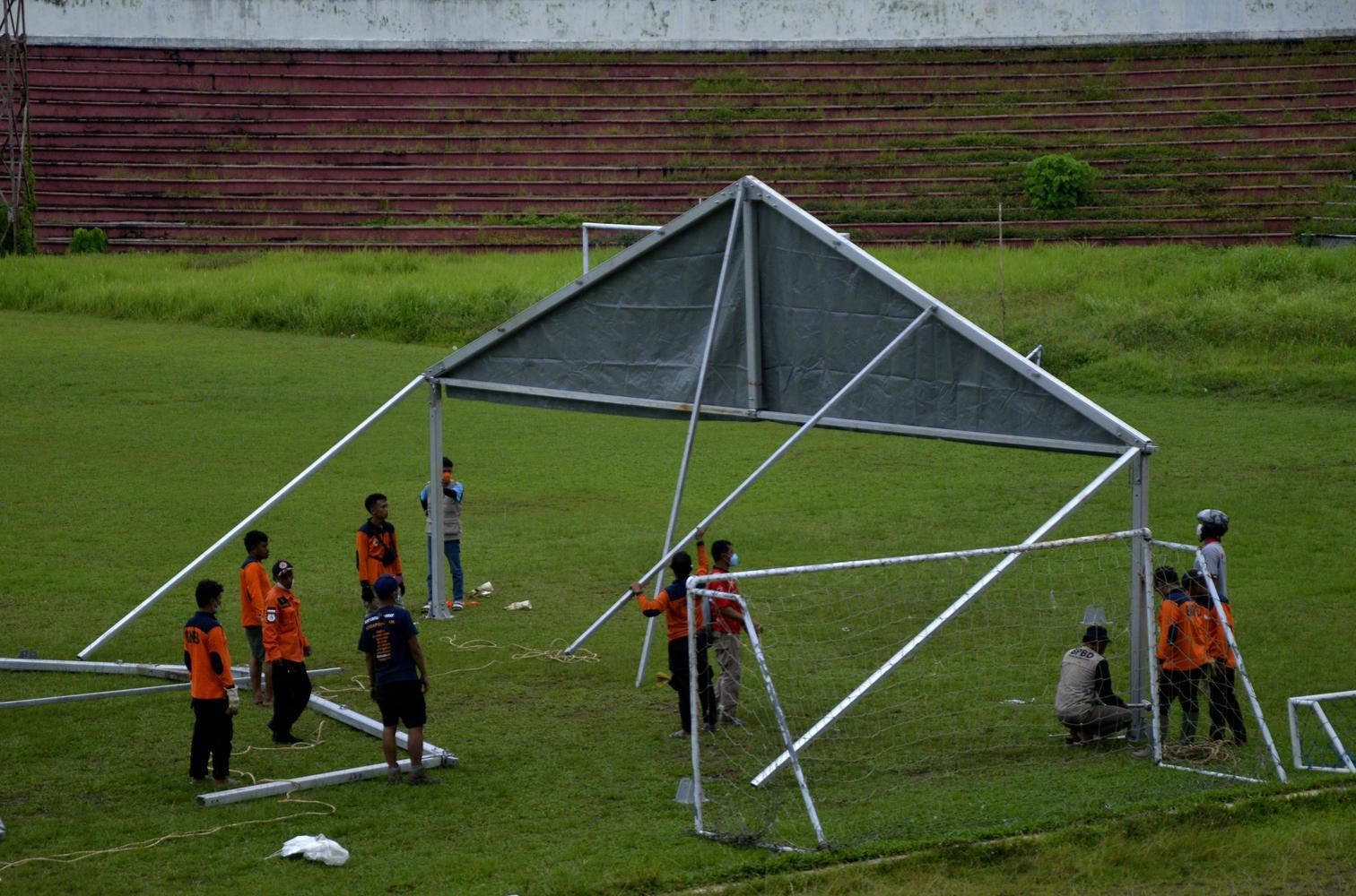 Sejumlah relawan dan tim SAR gabungan mendirikan tenda posko pengungsian untuk warga korban gempa bumi di Stadion Manakkara, Kabupaten Mamuju, Sulawesi Barat, Minggu (17/1/2021).