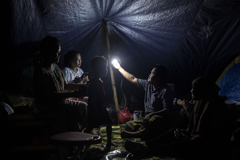 Pengungsi korban gempa bumi menyalakan lampu untuk menerangi tenda darurat yang dihuni keluarganya di kompleks Stadion Manakarra, Mamuju, Sulawesi Barat, Minggu (17/1/2021). BNPB menyatakan berdasarkan data per 17 Januari pukul 14.00 WIB jumlah korban gempa bumi Sulawesi Barat yang meninggal berjumlah 73 orang dan sebanyak 27.850 orang mengungsi di 25 titik pengungsian.