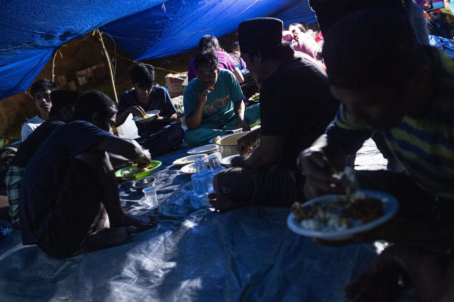 Sejumlah pengungsi korban gempa makan malam di tenda darurat yang mereka buat di kompleks Stadion Manakarra, Mamuju, Sulawesi Barat, Minggu (17/1/2021). BNPB menyatakan berdasarkan data per 17 Januari pukul 14.00 WIB jumlah korban gempa bumi Sulawesi Barat yang meninggal berjumlah 73 orang dan sebanyak 27.850 orang mengungsi di 25 titik pengungsian.