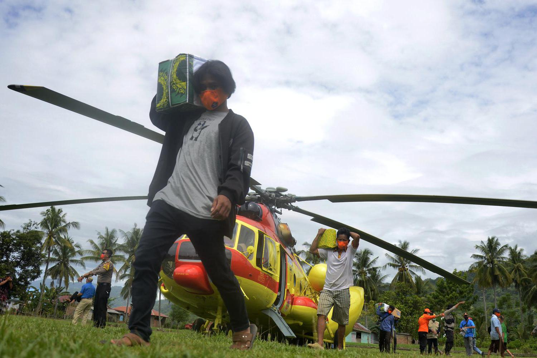 Sejumlah warga korban gempa bumi memindahkan bantuan logistik dari helikopter Badan Nasional Penanggulangan Bencana (BNPB) yang mendarat di Kecamatan Malunda, Kabupaten Majene, Sulawesi Barat, Rabu (20/1/2021). BNPB menyiapkan tujuh helikopter untuk membantu penyaluran bantuan logistik dan evakuasi korban gempa di daerah terisolir yang terdampak gempa bumi di Sulawesi Barat.