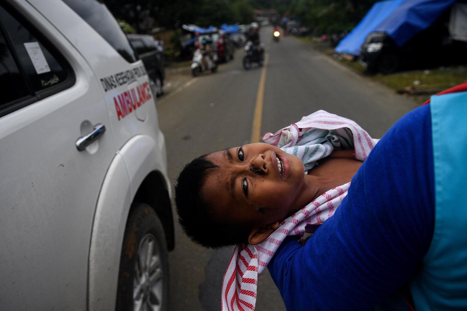 Tim medis membawa Syahgani (6), warga Desa Orobatu yang terluka karena tertimpa puing dampak gempa bumi di Tapalang, Mamuju, Sulawesi Barat, Rabu (20/1/2021). Syahgani dan ibunya Nurliati dirujuk ke rumah sakit untuk mendapatkan perawatan lebih lanjut, sementara ayahnya meninggal dunia saat gempa magnitudo 6,2 mengguncang daerah tersebut.