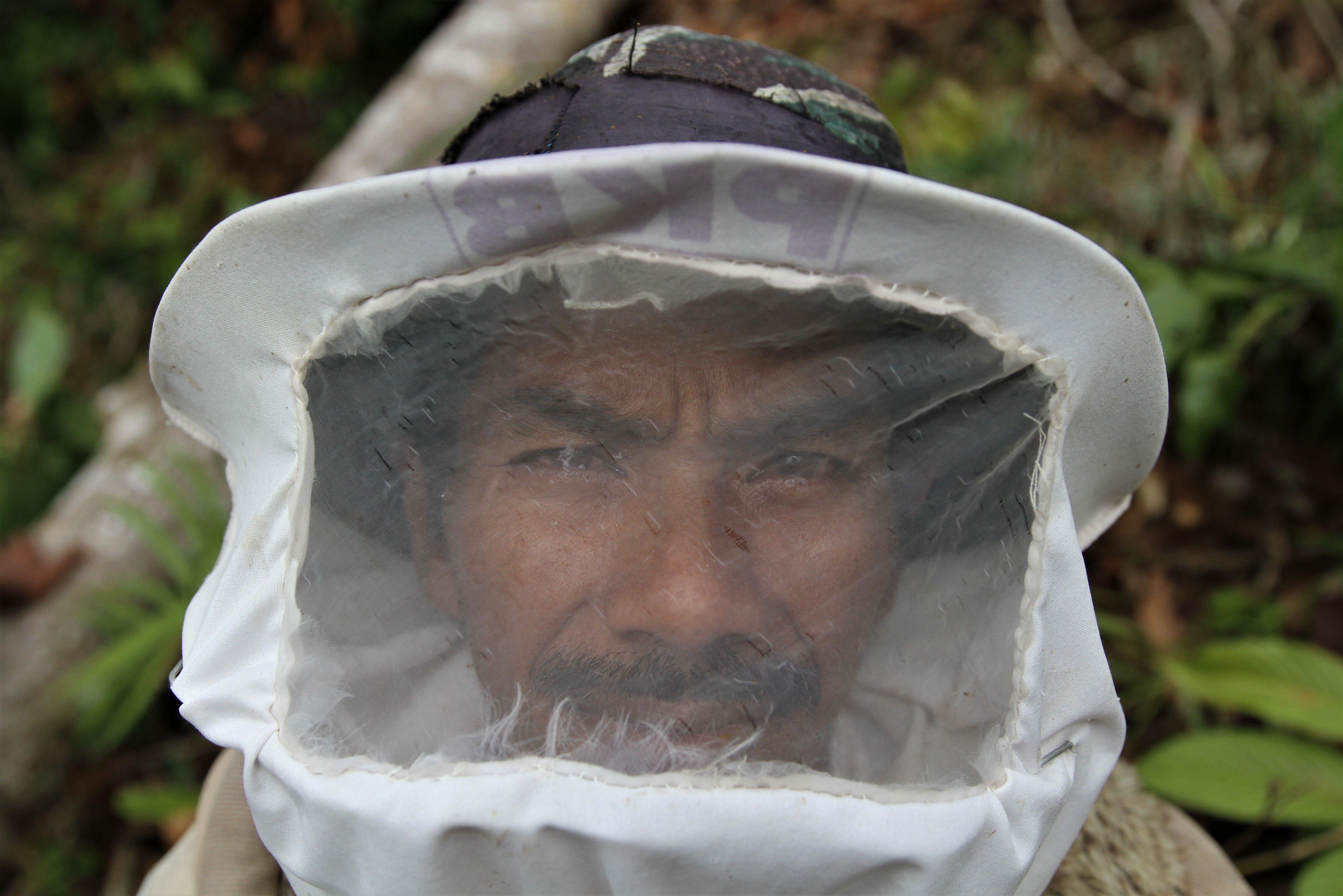 Triono mengenakan pengaman yang dibuatnya sendiri agar terhindar dari sengatan lebah tawong gong saat berada di kawasan Gunung Landono di Desa Landono 2, Kecamatan Landono, Konawe Selatan, Sulawesi Tenggara.