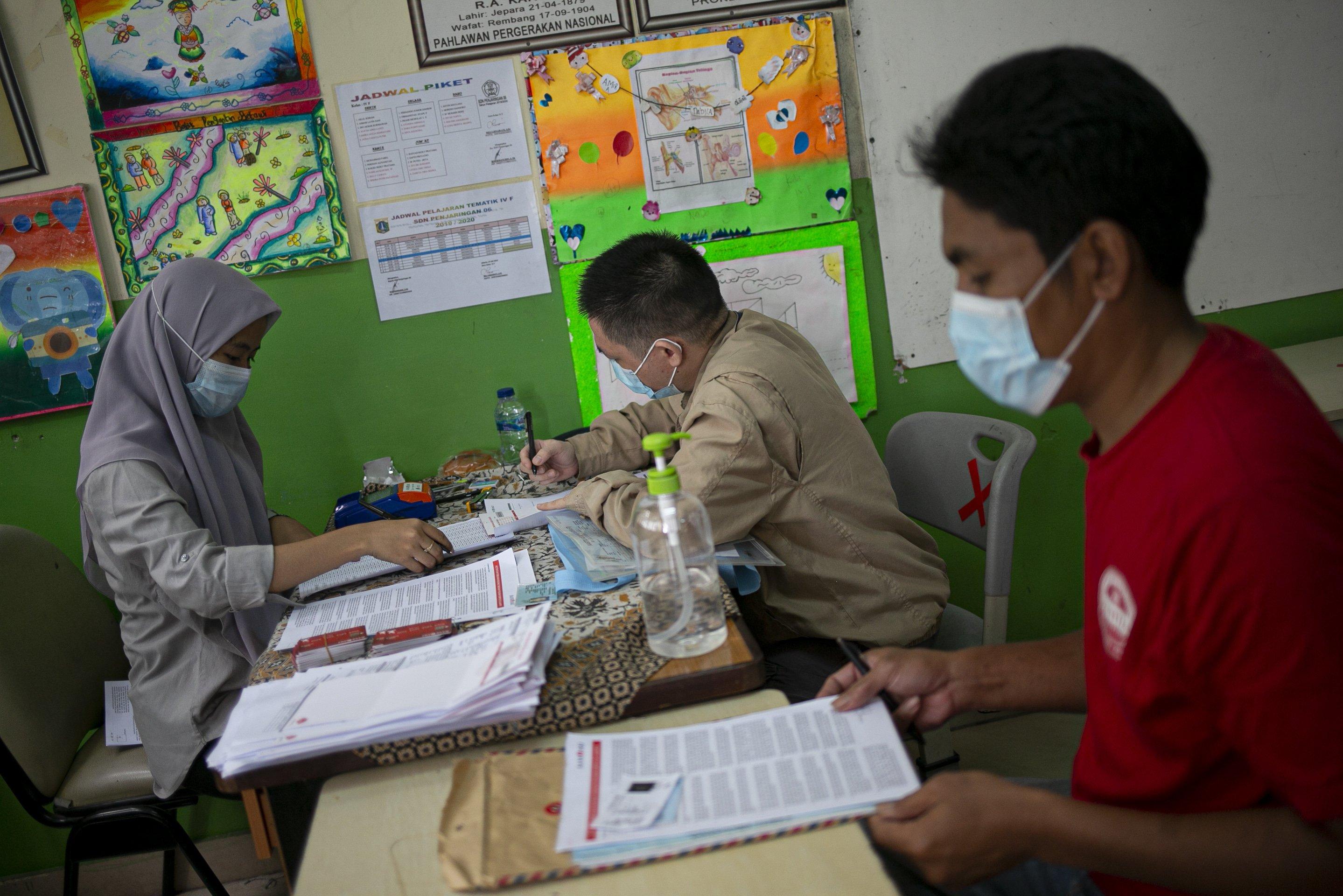 Petugas mandata warga saat mengambil Bantuan Sosial Tunai (BST) di SDN Penjaringan 06 Pagi, Jakarta Utara, Selasa (19/1/2021). Pemprov DKI Jakarta menyalurkan BST sebesar Rp300 ribu per KK kepada 1.055.216 KK mulai Januari hingga April 2021.