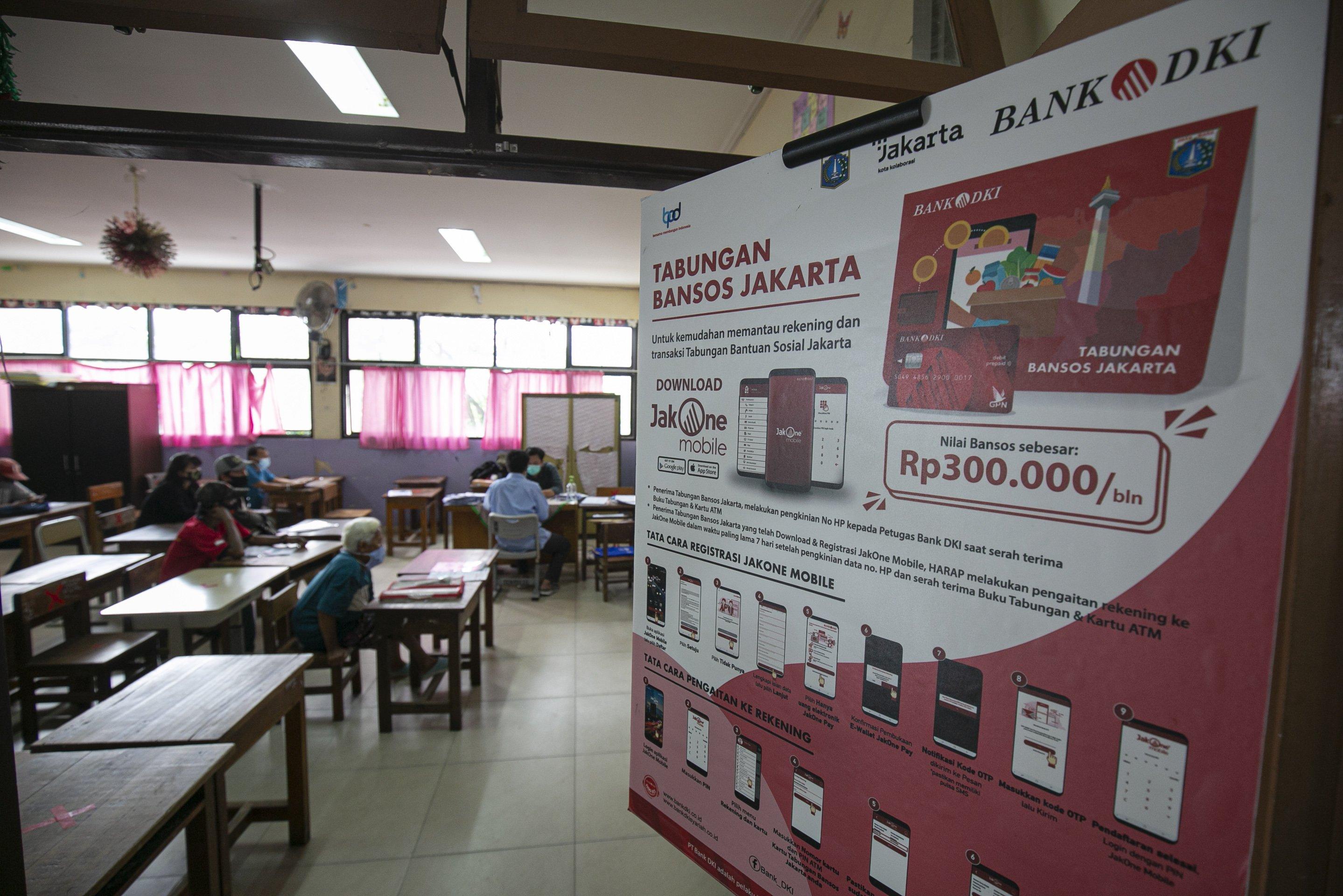 Warga mengisi dokumen persyaratan saat mengambil Bantuan Sosial Tunai (BST) di SDN Penjaringan 06 Pagi, Jakarta Utara, Selasa (19/1/2021). Pemprov DKI Jakarta menyalurkan BST sebesar Rp300 ribu per KK kepada 1.055.216 KK mulai Januari hingga April 2021.