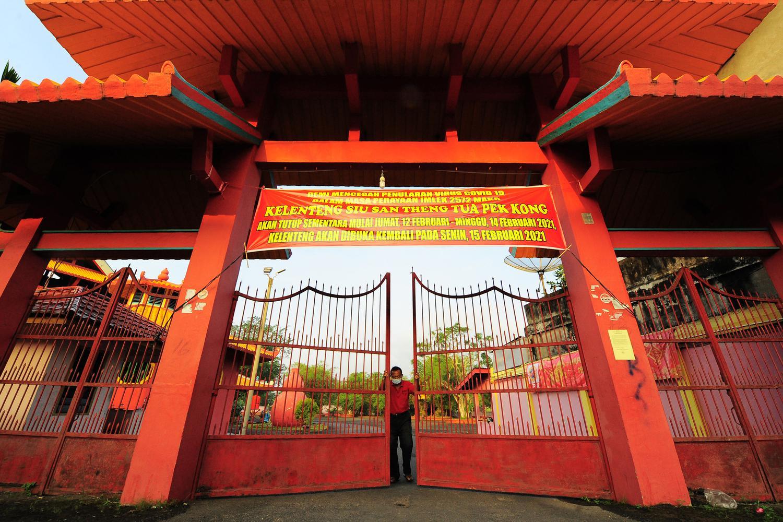 Pengurus menutup pagar Kelenteng Siau San Theng Tua Pek Kong saat Tahun Baru Imlek 2572/2021 di Kampung Manggis, Jambi, Jumat (12/2/2021). Sebagian kelenteng dan vihara di daerah itu ditutup pada 12-14 Februari guna mengantisipasi penyebaran COVID-19.