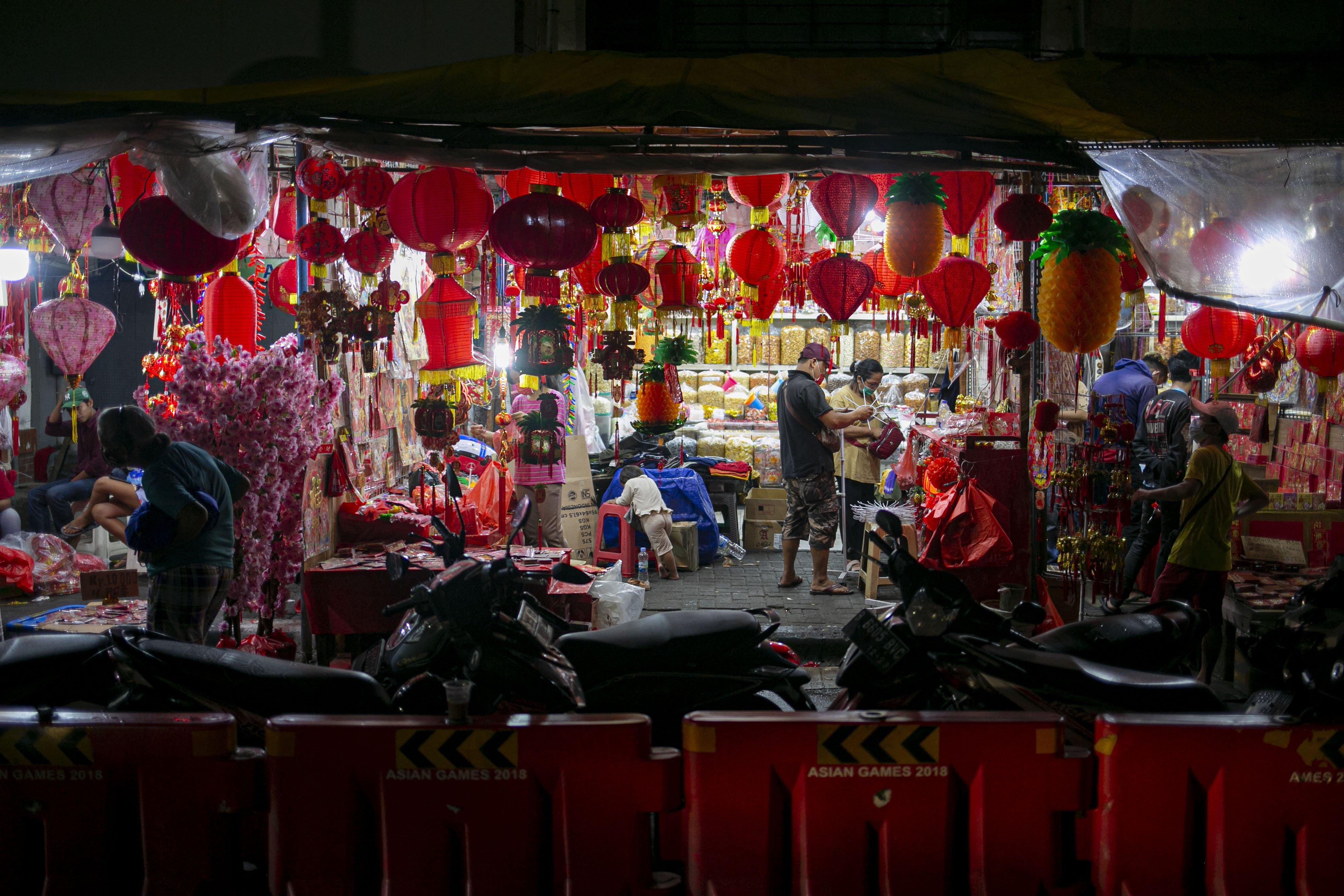 Pedagang merapikan pernak pernik Imlek yang dijual di Pasar Glodok, Jakarta, Kamis (11/2/2021). Pedagang di lokasi tersebut mengaku penjualan tahun ini anjlok hingga 80 persen dibandingkan tahun lalu akibat pandemi COVID 19.