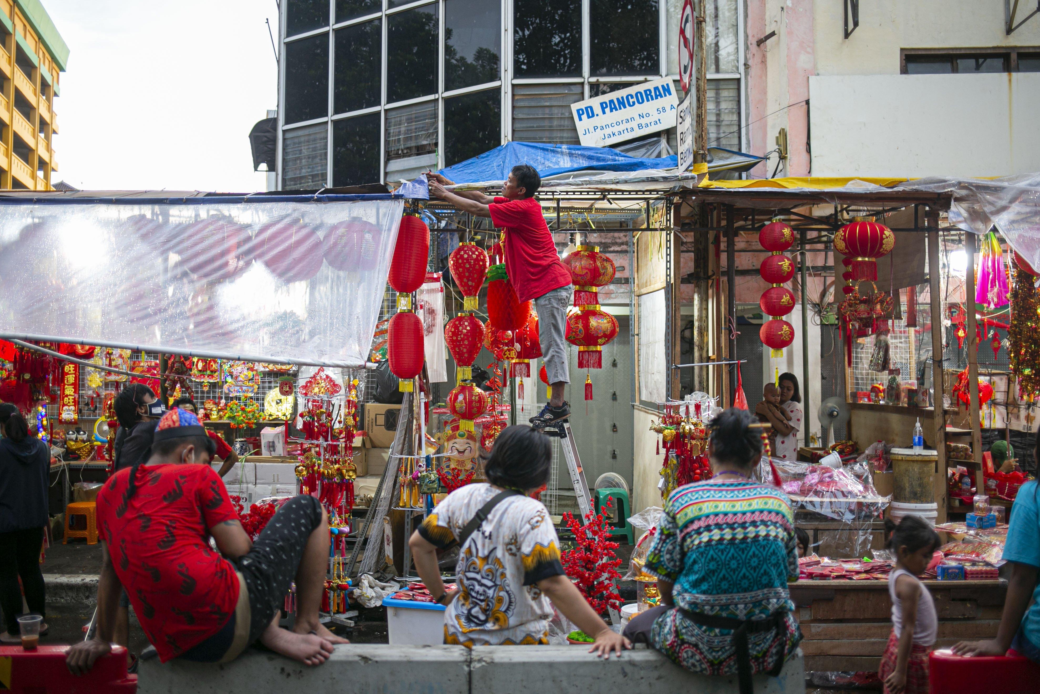 Pedagang merapikan kios pernak-pernik Imlek yang dijual di Pasar Glodok, Jakarta, Kamis (11/2/2021). Pedagang di lokasi tersebut mengaku penjualan tahun ini anjlok hingga 80 persen dibandingkan tahun lalu akibat pandemi COVID 19.