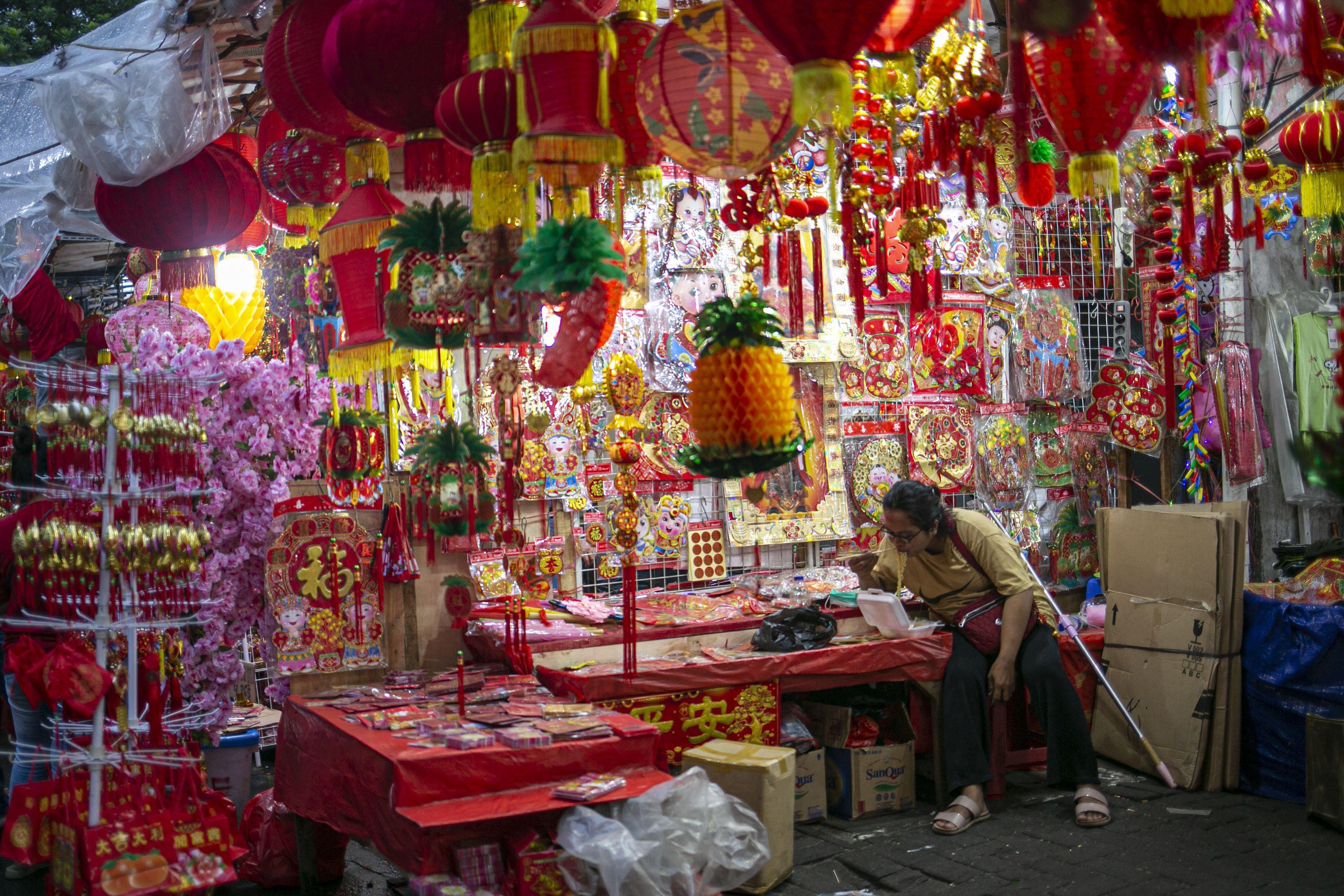 Pedagang menyantap makanan dikios pernak-pernik Imlek yang dijual di Pasar Glodok, Jakarta, Kamis (11/2/2021). Pedagang di lokasi tersebut mengaku penjualan tahun ini anjlok hingga 80 persen dibandingkan tahun lalu akibat pandemi COVID 19.