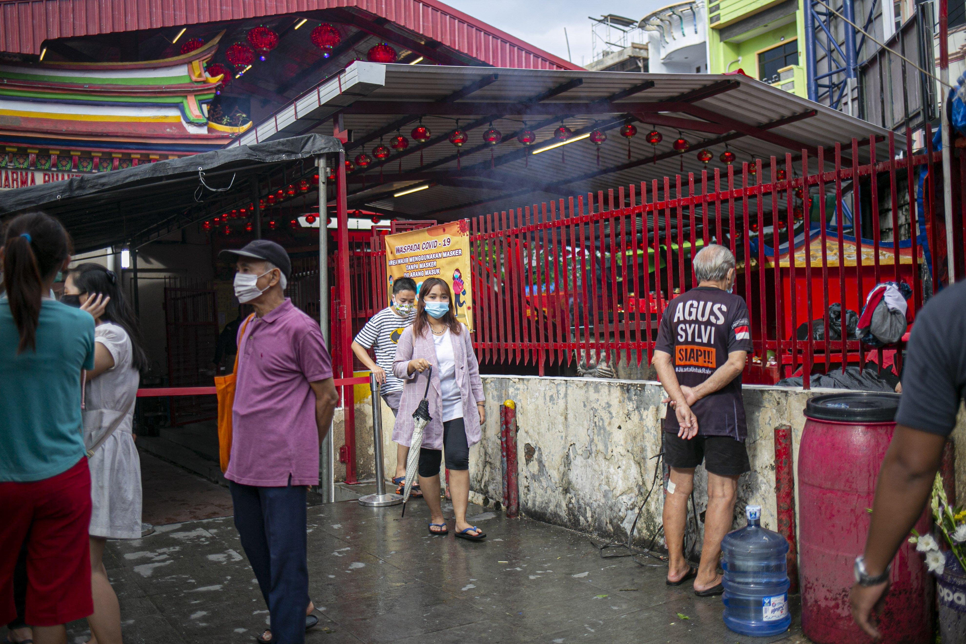 Warga keturunan Tionghoa keluar dari Vihara Dharma Bhakti, Kawasan Petak Sembilan, Glodok, Jakarta, Kamis (11/2/2021). Vihara tersebut menerapkan pembatasan waktu sembahyang serta mewajibkan menjaga jarak dan memakai masker saat sembahyang untuk mencegah penyebaran COVID-19.