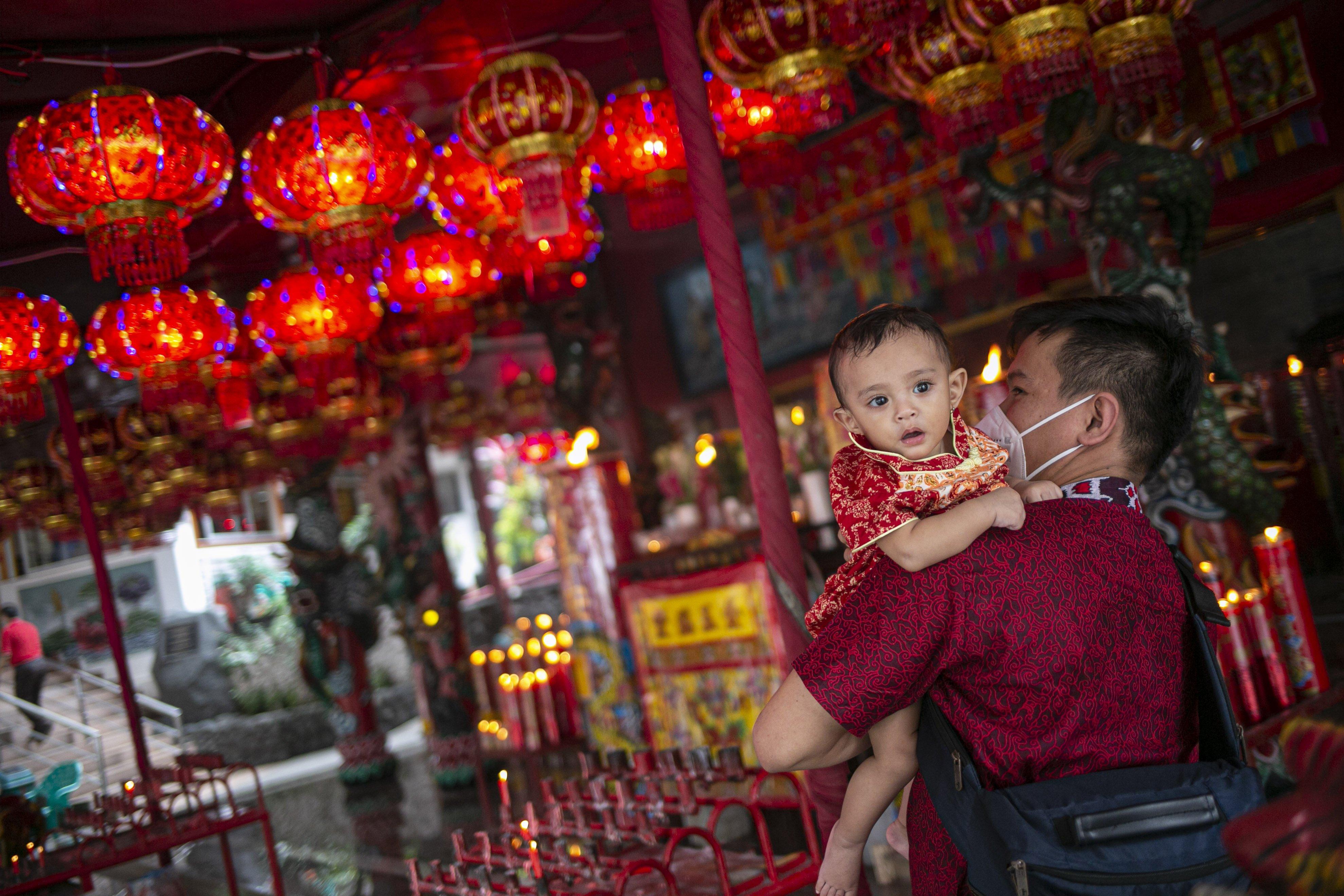 Warga keturunan Tionghoa bersama anaknya menyambut tahun baru Imlek 2572 di Vihara Amurva Bhumi, Jakarta, Kamis (11/2/2021).
