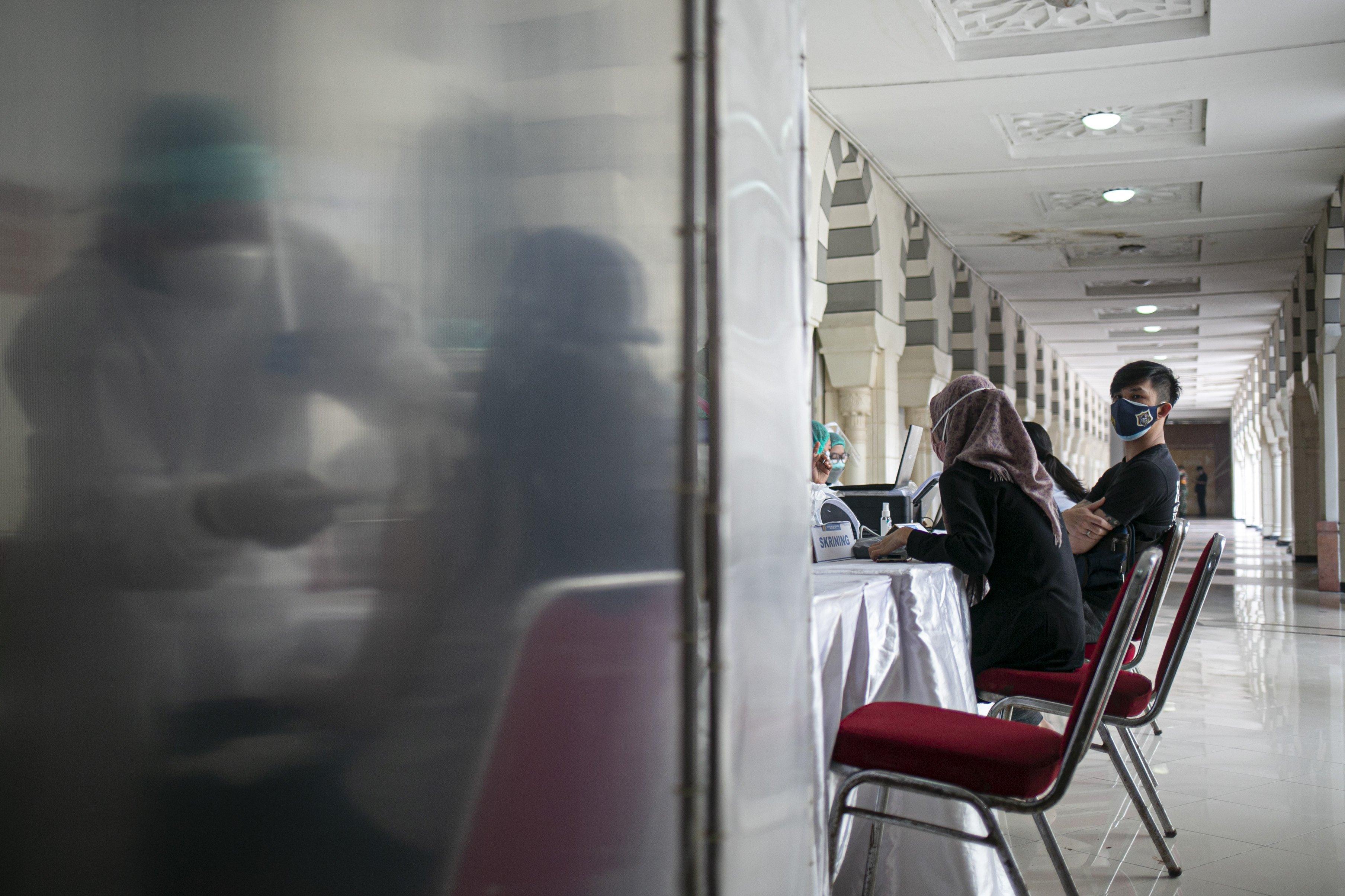 Petugas medis menyuntikan vaksin covid-19 kepada pedagang di Pasar Tanah Abang Blok A, Jakarta, Rabu (17/2/2021). Vaksinasi covid-19 tahap kedua yang diberikan untuk pekerja publik dan lansia itu dimulai dari pedagang Pasar Tanah Abang.