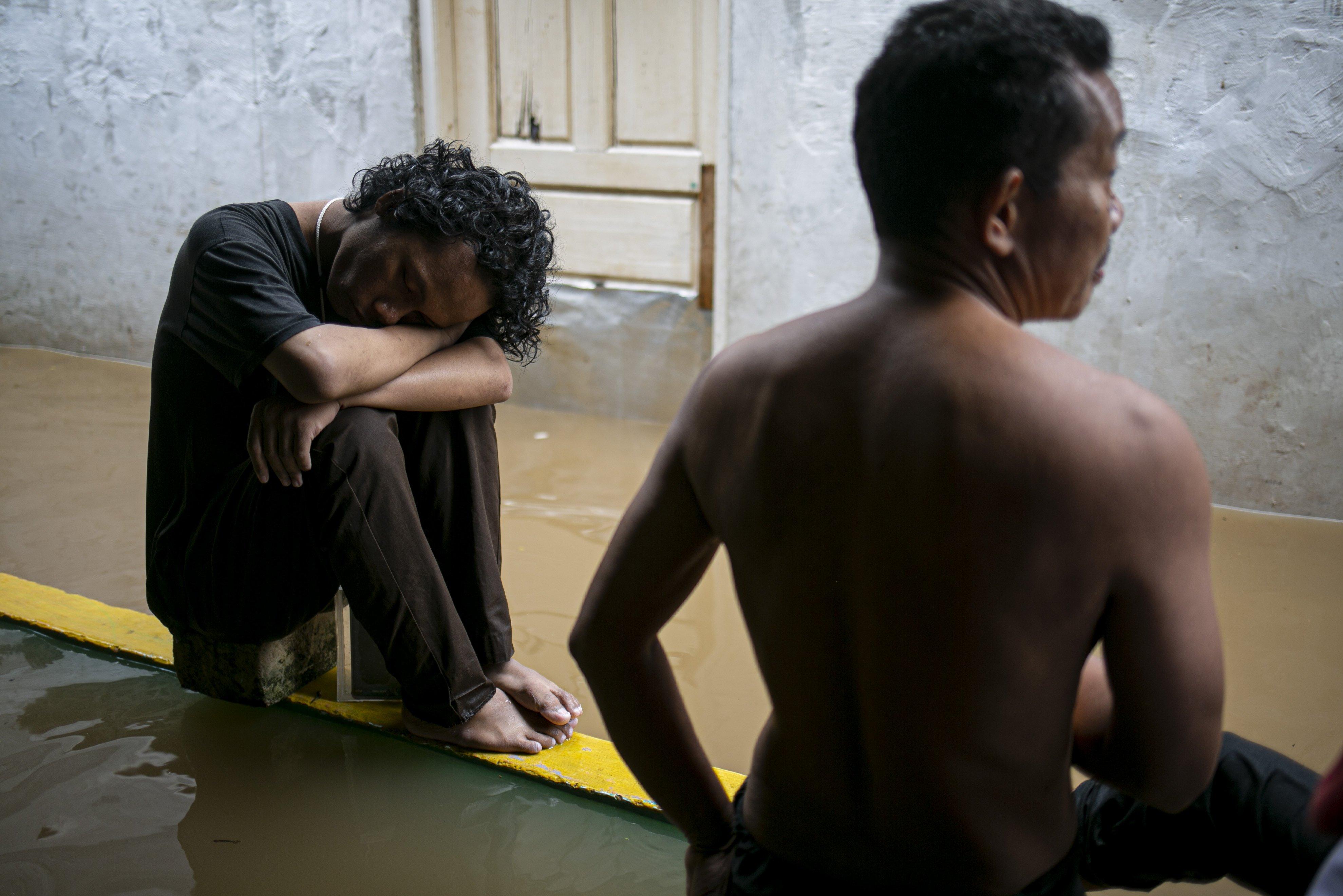 Warga tertidur didepan rumahnya yang tergenang banjir di kawasan Cipinang Melayu, Jakarta Timur, Jumat (19/2/2021). Banjir di kawasan tersebut akibat curah hujan yang tinggi dan meluapnya air dari Kali Sunter.