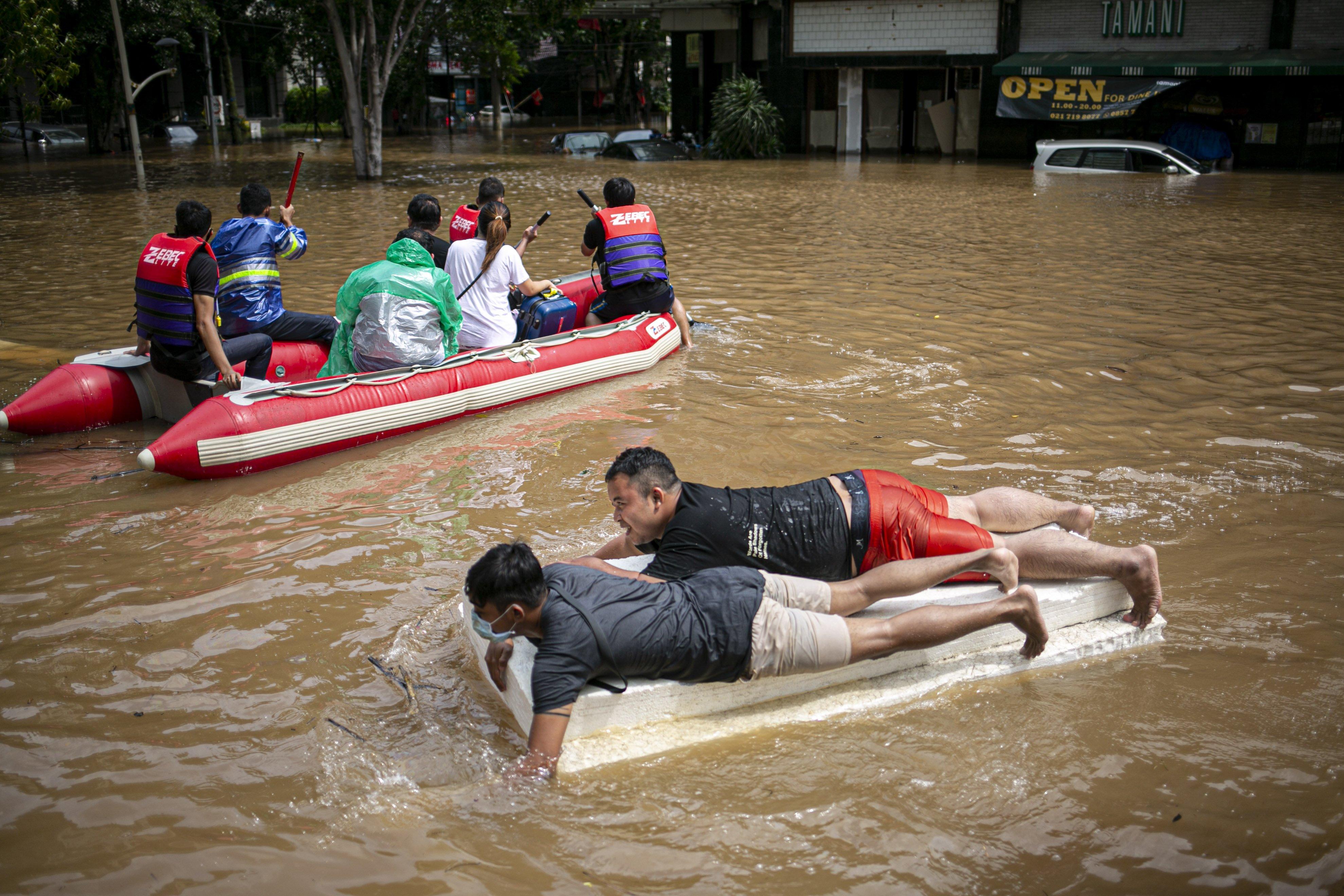 Warga melewati banjir menggunakan perahu buatan di kawasan Kemang, Jakarta Selatan, Sabtu (20/2/2021). Banjir yang terjadi akibat curah hujan tinggi serta drainase yang buruk membuat kawasan Kemang banjir setinggi 1,5 meter.