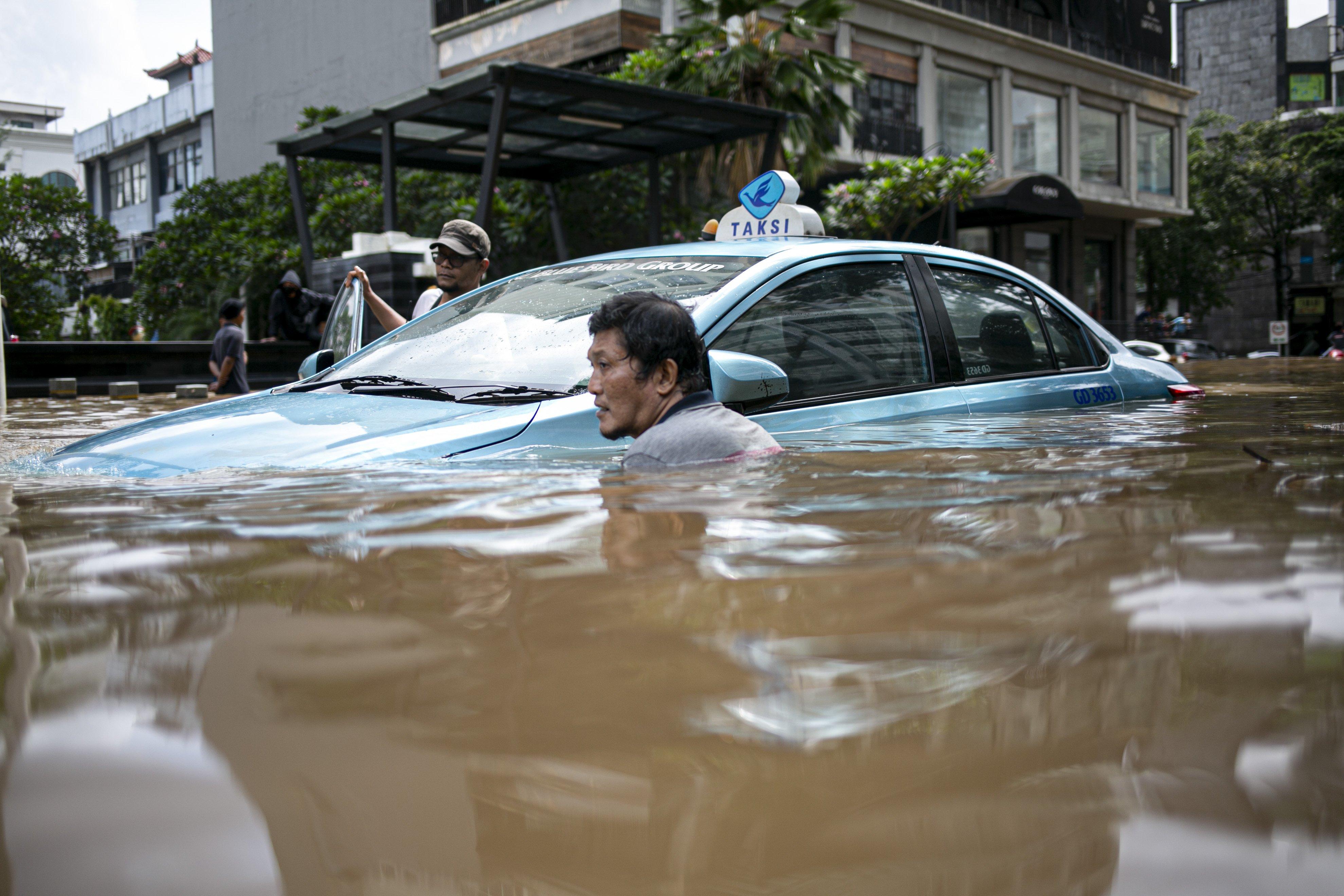 Warga berusaha mengevakuasi mobil yang terendam banjir di kawasan Kemang, Jakarta Selatan, Sabtu (20/2/2021). Banjir yang terjadi akibat curah hujan tinggi serta drainase yang buruk membuat kawasan Kemang banjir setinggi 1,5 meter.