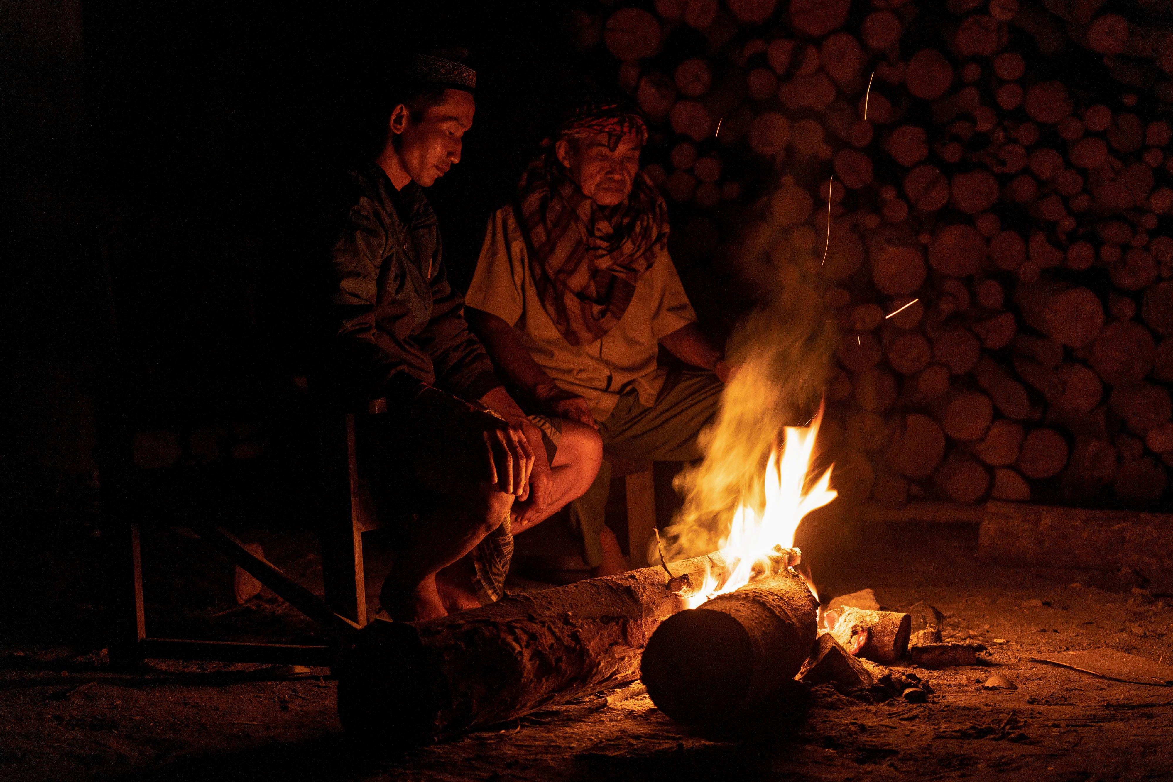 Dua warga duduk di depan api unggun saat meronda di Ngrangkah, Umbulharjo, Cangkringan, Sleman, DI Yogyakarta.