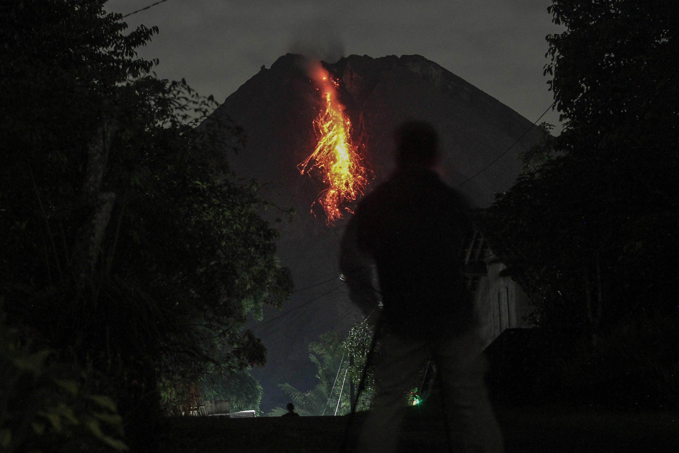 Relawan menyaksikan guguran lava dari Turi, Sleman, DI Yogyakarta.