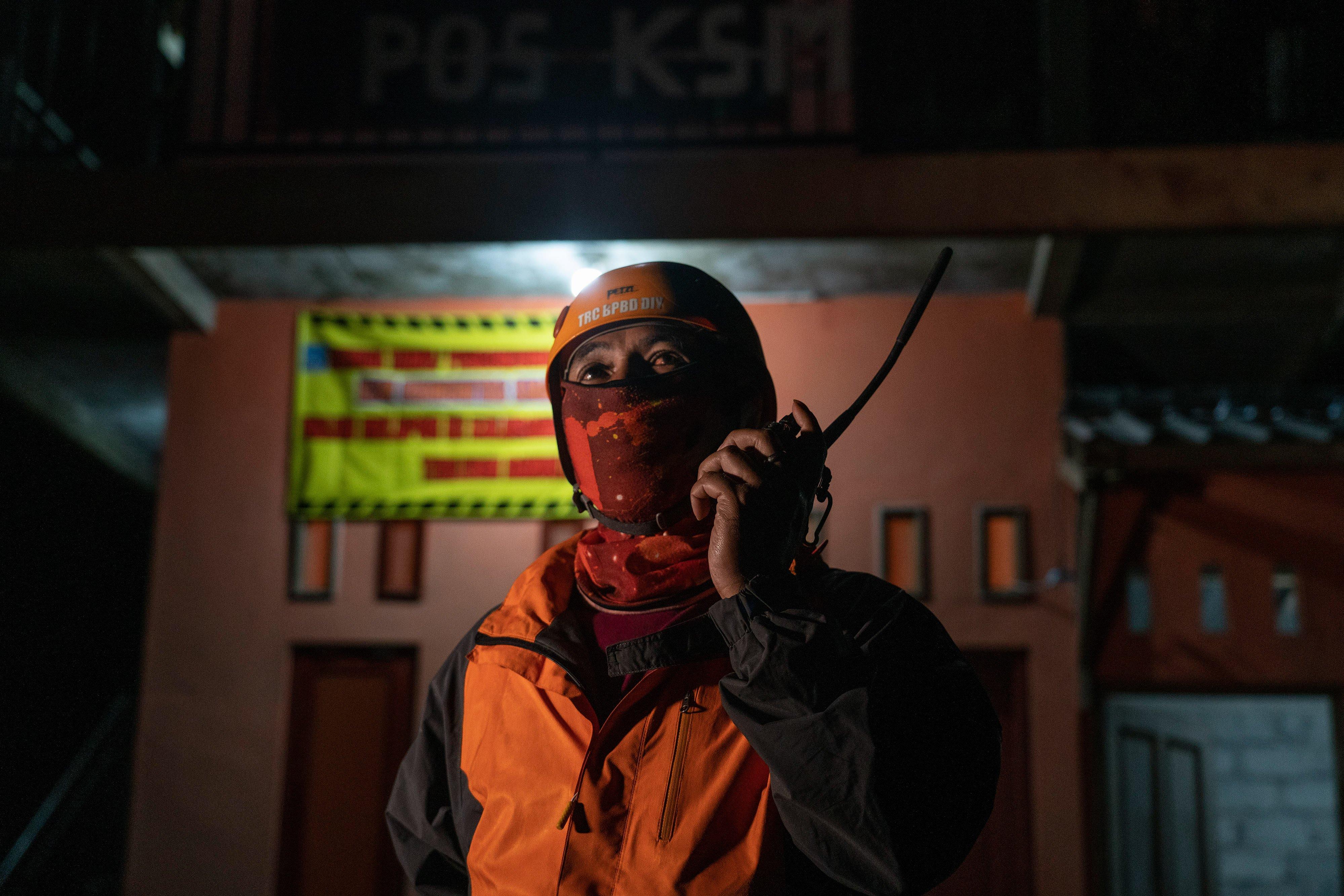 Anggota Tim Reaksi Cepat (TRC) BPBD DIY berkomunikasi menggunakan radio komunikasi di pos pantau Desa Glagaharjo, Cangkringan, Sleman, DI Yogyakarta.