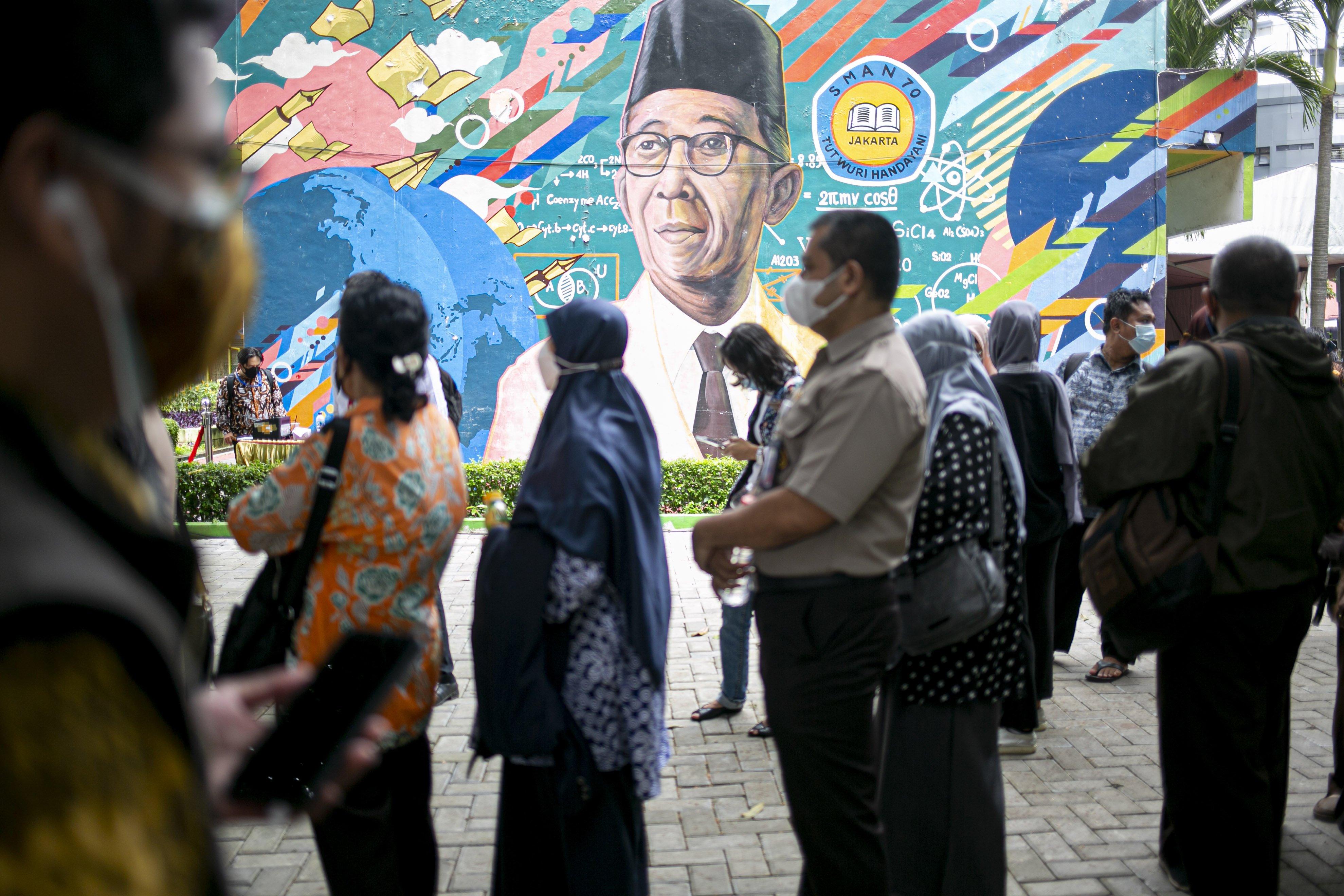 Sejumlah tenaga pendidikan mengantre mendaftar vaksinasi COVID-19 di SMA Negeri 70 Jakarta, Jakarta, Rabu (24/2/2021). Pemerintah memulai tahap vaksinasi untuk guru, tenaga kependidikan, dan dosen dengan target sebanyak 5.057.582 orang se-Indonesia.