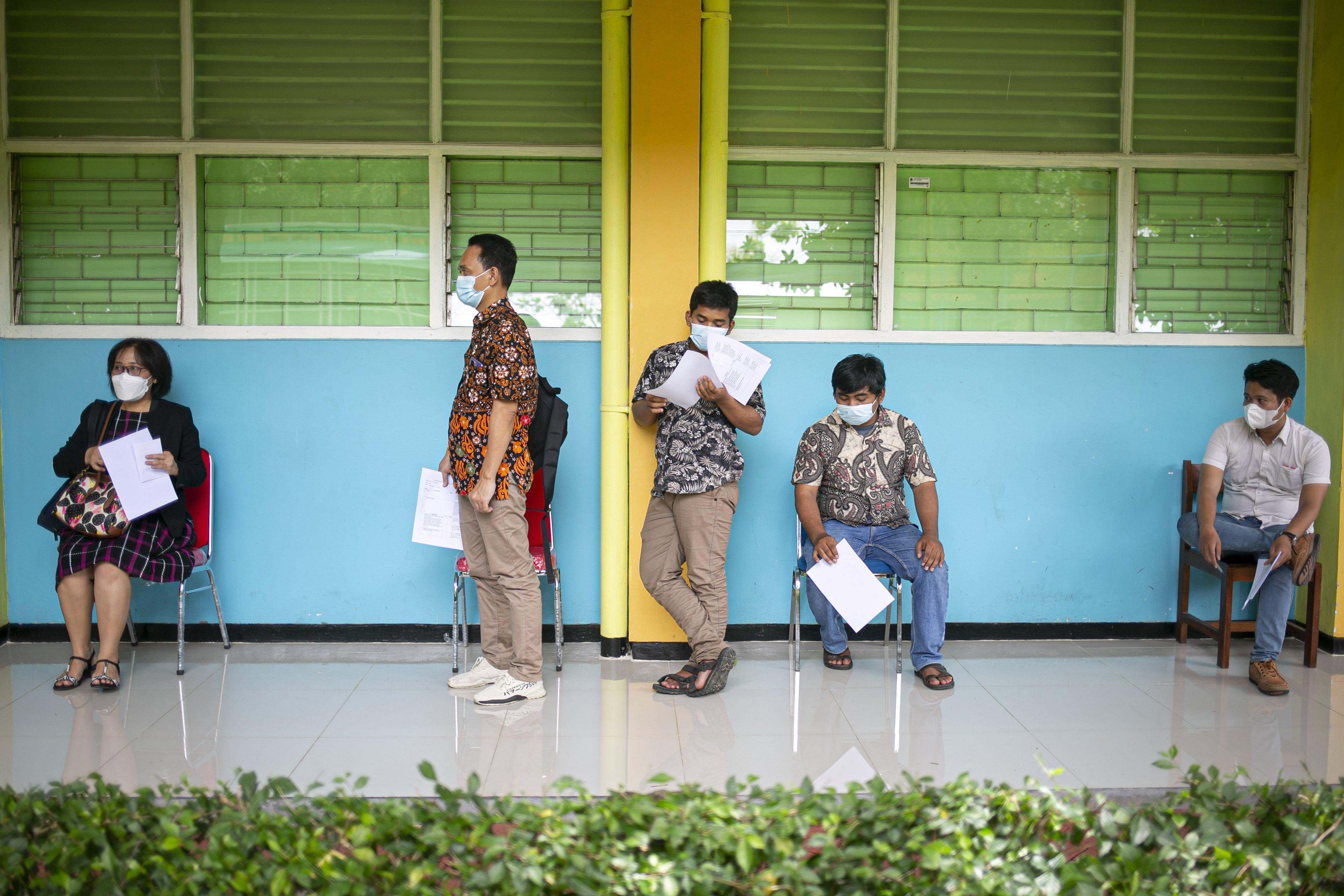 Sejumlah tenaga pendidikan mengantre vaksinasi massal COVID-19 di SMA Negeri 70 Jakarta, Jakarta, Rabu (24/2/2021). Pemerintah memulai tahap vaksinasi untuk guru, tenaga kependidikan, dan dosen dengan target sebanyak 5.057.582 orang se-Indonesia.