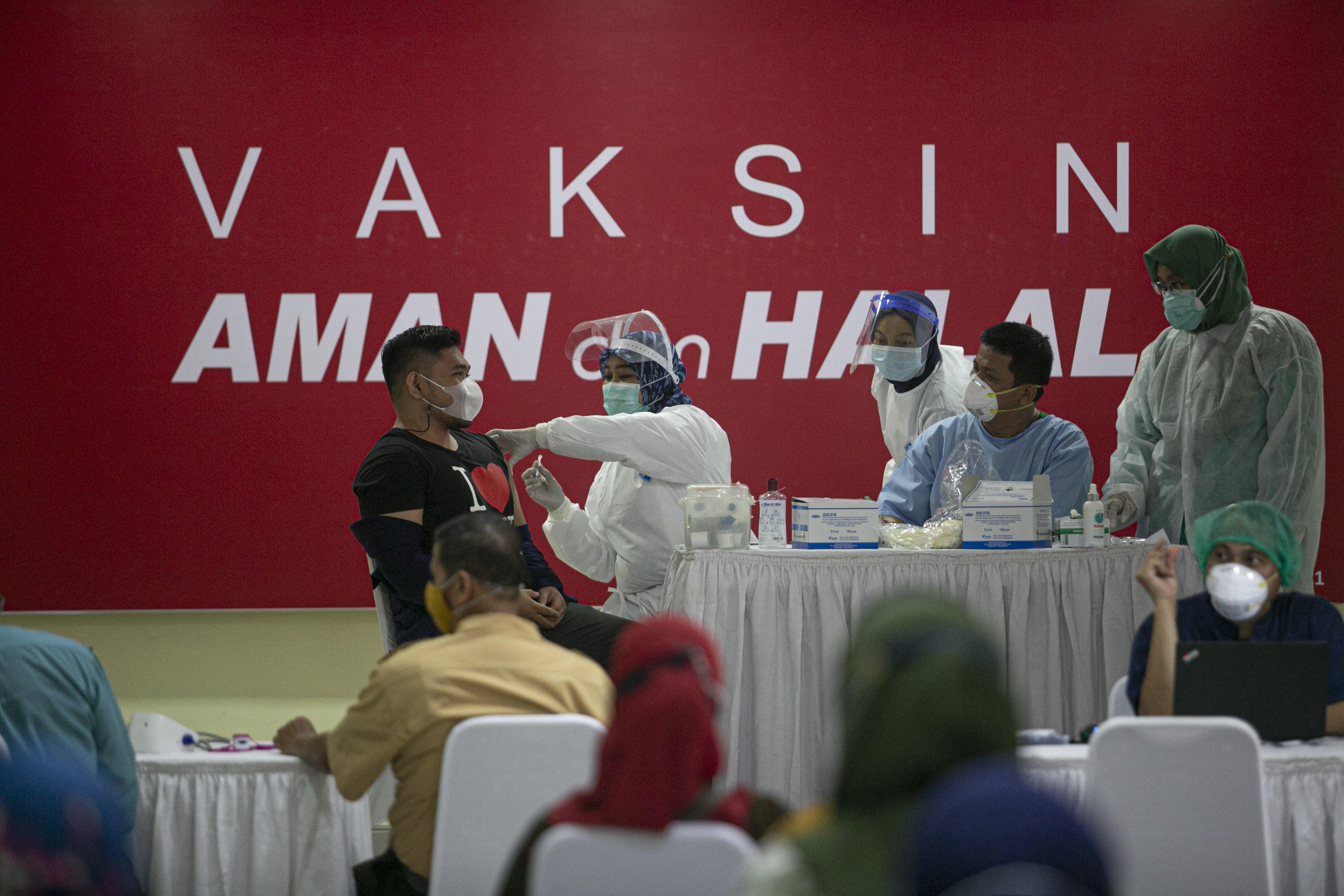 Petugas menyuntikkan vaksin COVID-19 kepada tenaga pengajar dalam acara vaksinasi massal di SMA Negeri 70 Jakarta, Jakarta, Rabu (24/2/2021). Pemerintah memulai tahap vaksinasi untuk guru, tenaga kependidikan, dan dosen dengan target sebanyak 5.057.582 orang se-Indonesia.