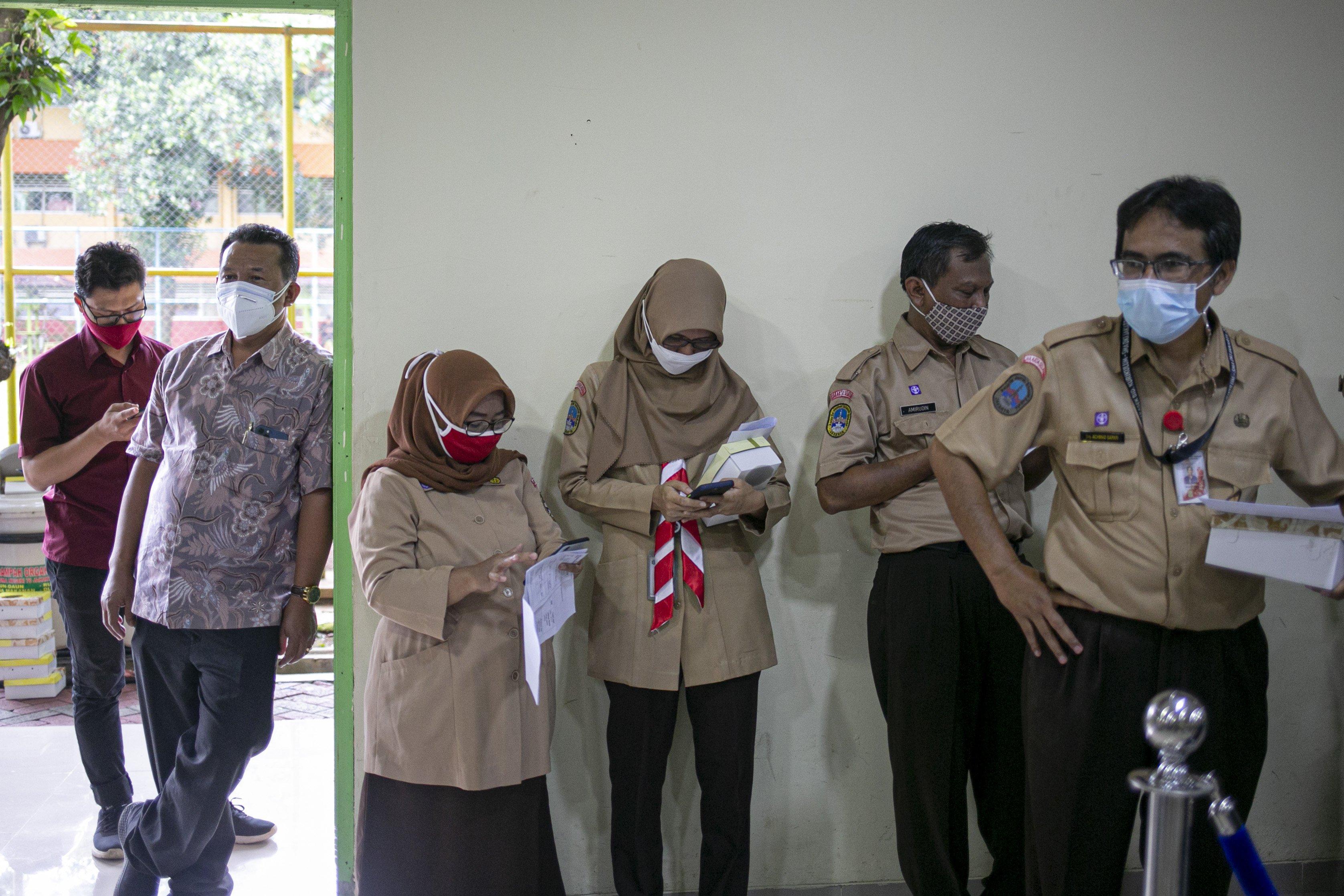 Sejumlah tenaga pendidikan mengantre vaksinasi COVID-19 di SMA Negeri 70 Jakarta, Jakarta, Rabu (24/2/2021). Pemerintah memulai tahap vaksinasi untuk guru, tenaga kependidikan, dan dosen dengan target sebanyak 5.057.582 orang se-Indonesia.
