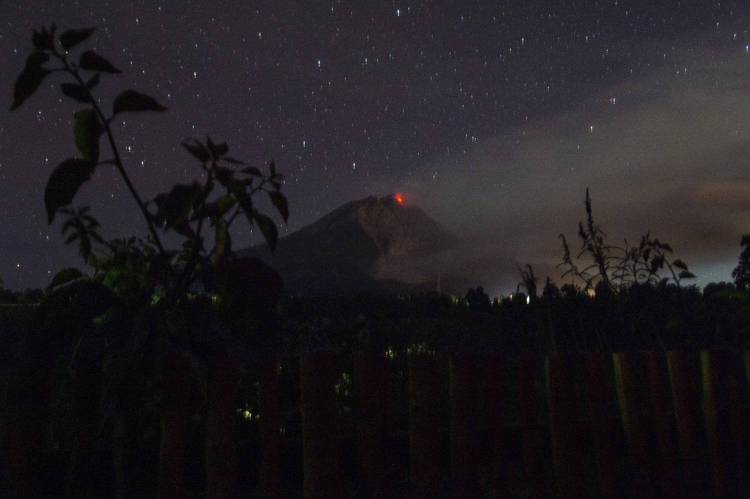 Guguran lava dari puncak Gunung Sinabung terlihat dari di Desa Tigapancur, Simpang Empat, Karo, Sumatera Utara, Kamis (25/2/2021). Pusat Vulkanologi dan Mitigasi Bencana Geologi (PVMBG) di Pos Pemantauan Gunung Api Sinabung mencatat volume kubah lava di puncaknya sudah mencapai 4 juta meter kubik sehingga diimbau untuk warga yang berada pada radius 2.5 kilometer dalam zona merah untuk tidak melakukan aktivitas.