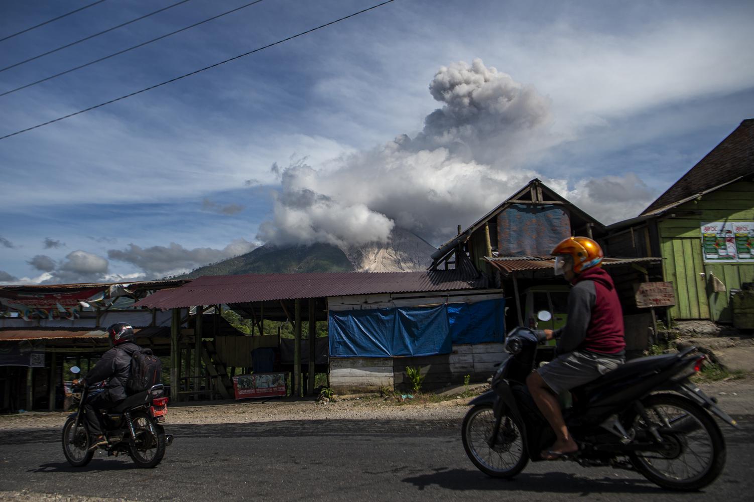 Sejumlah kendaraan melintas dengan latar Gunung Sinabung yang menyemburkan material vulkanik saat erupsi di Desa Tigapancur, Simpang Empat, Karo, Sumatera Utara, Kamis (25/2/2021). Gunung Sinabung erupsi dengan tinggi kolom 1.500 meter di atas puncak atau sekitar 3.960 meter di atas permukaan laut.