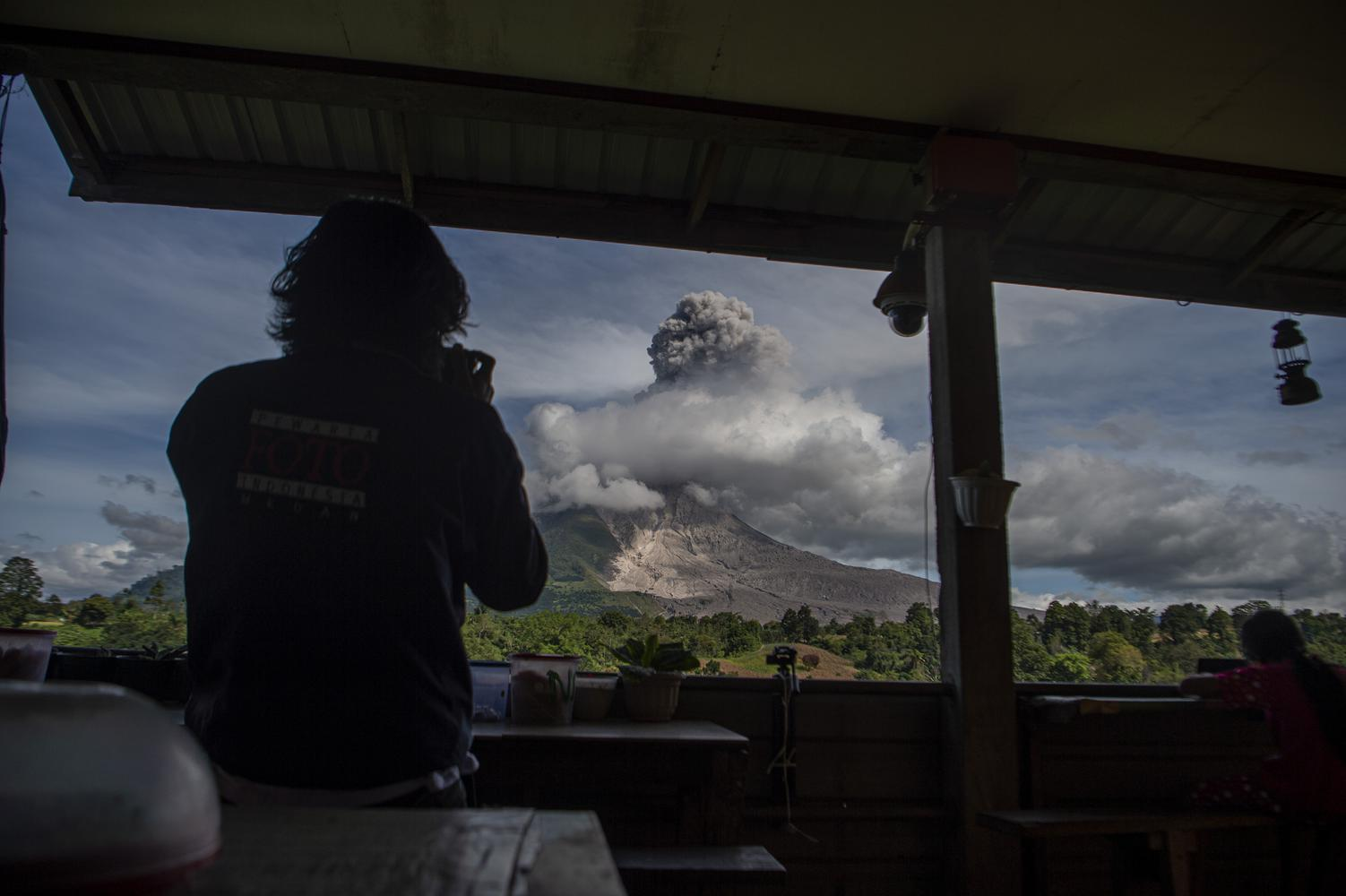 Wartawan mengambil foto Gunung Sinabung yang menyemburkan material vulkanik saat erupsi di Desa Tigapancur, Simpang Empat, Karo, Sumatera Utara, Kamis (25/2/2021). Gunung Sinabung erupsi dengan tinggi kolom 1.500 meter di atas puncak atau sekitar 3.960 meter di atas permukaan laut.