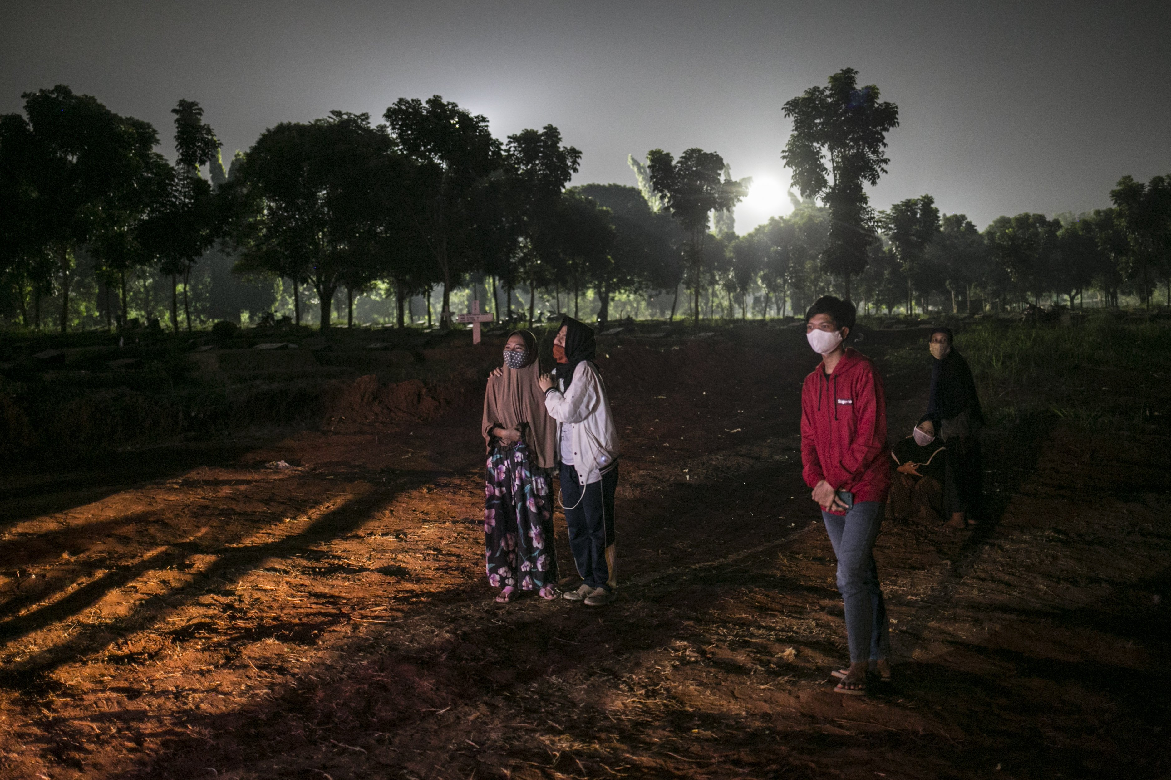 Keluarga korban covid-19 menyaksikan pemakaman keluarganya dengan jarak yang jauh di TPU Pondok Rangon, Jakarta, Kamis (16/7/2020).